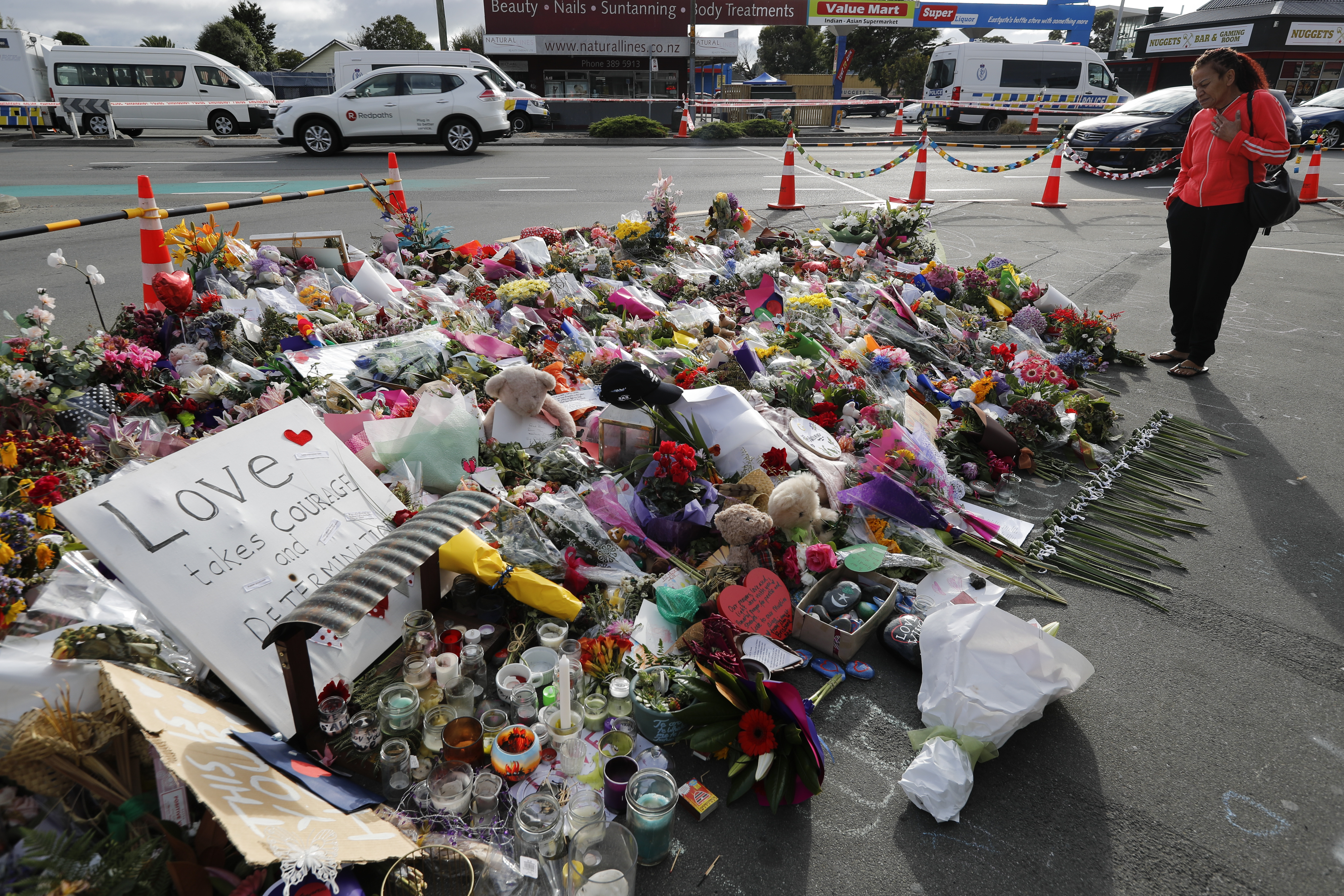 A woman looks at the floral tribute near the Linwood mosque in Christchurch, New Zealand, Thursday, March 21, 2019. Police officials in New Zealand say the man responsible for killing 50 people at two mosques was on his way to a third attack when police arrested him. (AP Photo/Vincent Thian)
