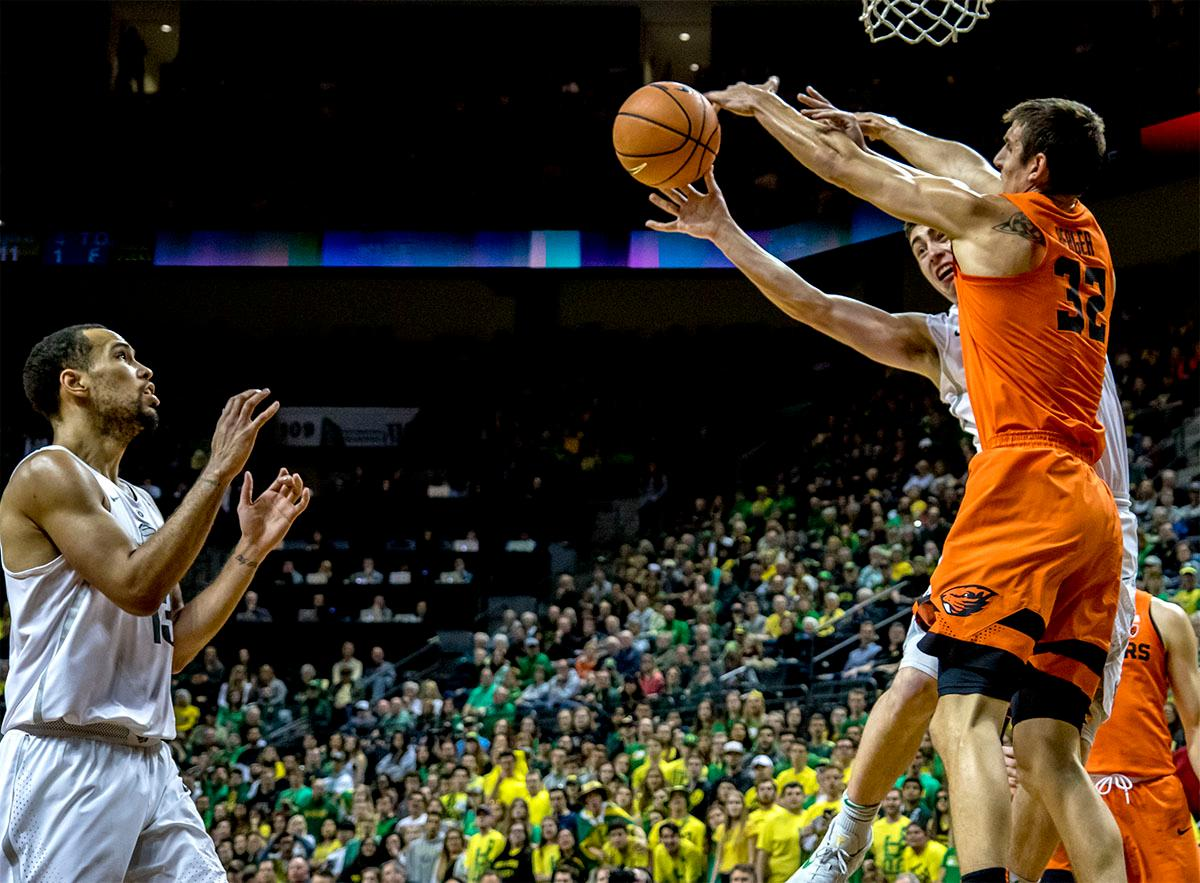 The Duck's Payton Pritchard (#3) tosses the ball aside to teammate Paul White (#13) to shoot for the basket. The Ducks defeated the Beavers in the civil war game, 66-57, at Matthew Knight Arena on Saturday night. Elijah Brown scored a game high of 20 points with 18 of the points coming in the first half, Paul White added 17 points. The Ducks are now 14-7 overall and 4-4 in conference play. The Ducks will next face California on Thursday Feb. 1 at 6:00 p.m. Photo by August Frank, Oregon News Lab