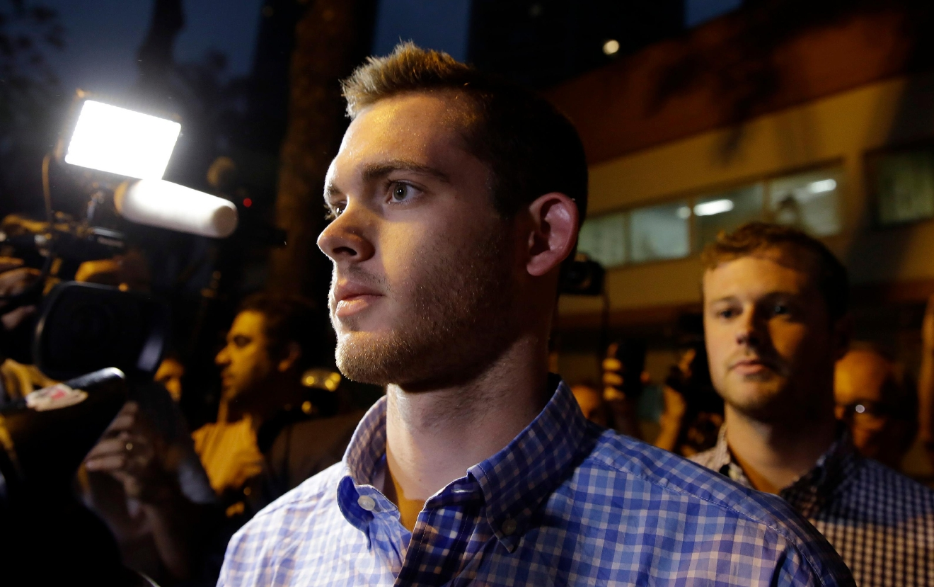 American Olympic swimmers Gunnar Bentz, front, and Jack Conger leave a police station in the Leblon neighborhood of Rio de Janeiro, Brazil, Thursday, Aug. 18, 2016. The two were taken off their flight from Brazil to the U.S. on Wednesday by local authorities amid an investigation into a reported robbery targeting Ryan Lochte and his teammates. A Brazilian police officer told The Associated Press that Lochte fabricated a story about being robbed at gunpoint in Rio de Janeiro. (AP Photo/Leo Correa)