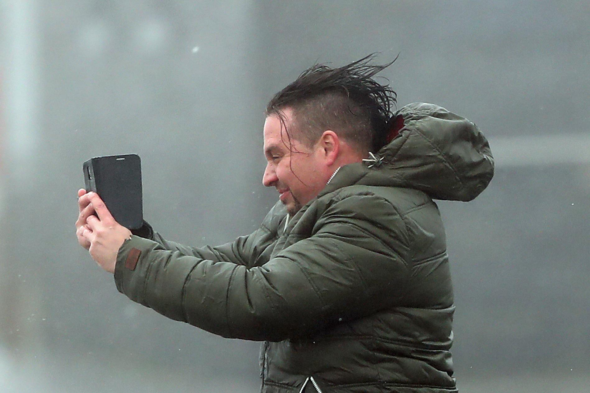 A man take selfie in the high wind at Lahinch on the west coast of Ireland  Monday Oct. 16, 2017, as the remnants of  Hurricane Ophelia begins to hit Ireland and parts of Britain. Ireland's meteorological service is predicting wind gusts of 120 kph to 150 kph (75 mph to 93 mph), sparking fears of travel chaos. Some flights have been cancelled, and aviation officials are warning travelers to check the latest information before going to the airport Monday.  (Niall Carson/PA via AP)