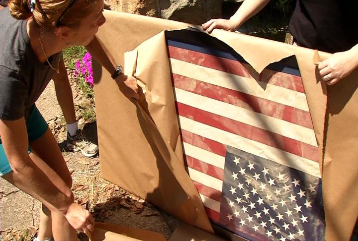 Marie Clark unwraps her American flag that was still hanging from her home when the June floodwaters receded. (WCHS/WVAH)