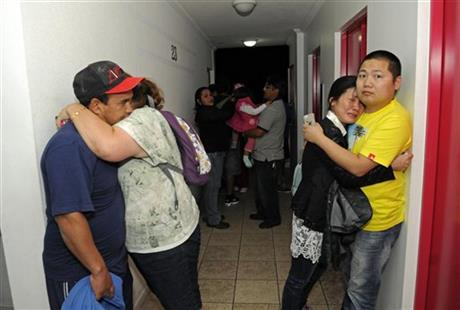 People embrace on the upper floor of an apartment building located a few blocks from the coast where they gathered to avoid a possible tsunami after an earthquake in Iquique, Chile, Tuesday, April 1, 2014.