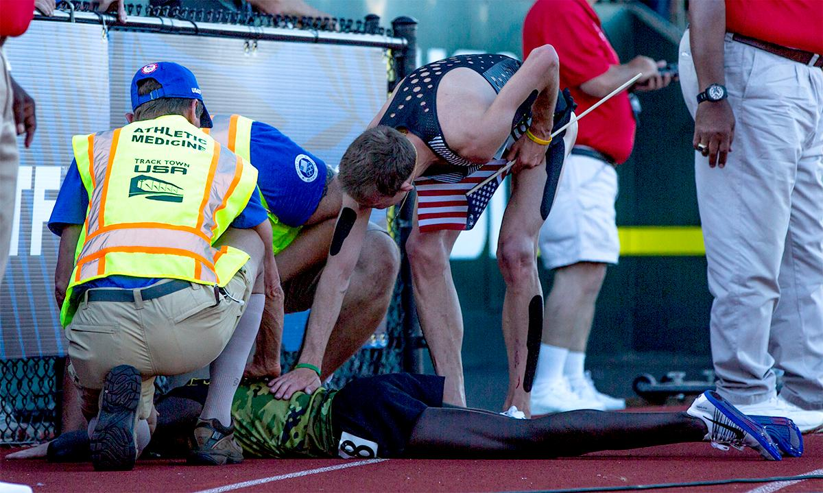 Nike Oregon Project's Galen Rupp gives second place Shadrack Kipchirchir a pat of congratulation after Kipchirchir collapsed at the side of the track upon finishing. Rupp won the 10,000 meter with a time of 27:55.04. Day one of the U.S. Olympic Trials Track and Field began on Friday at Hayward Field in Eugene, Oregon and will continue through July 10. Photo by August Frank, Oregon News Lab