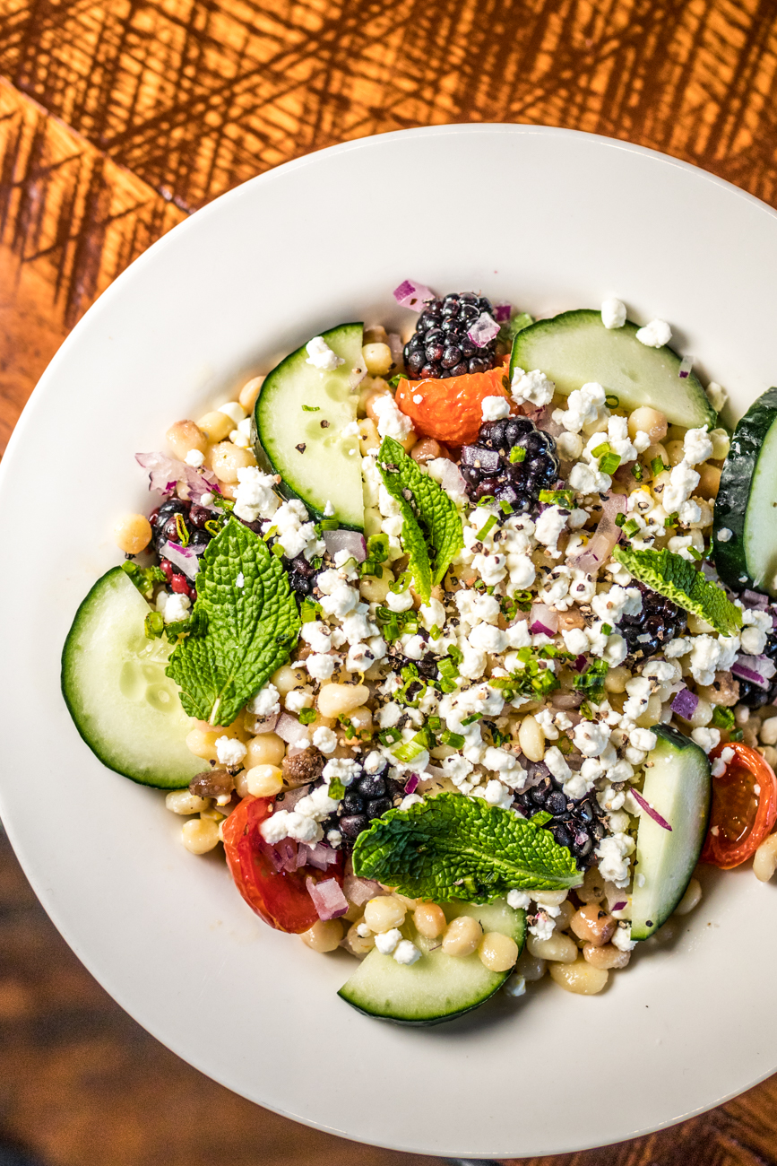 Fregola Salad: roasted cherry tomatoes, cucumber, onion, fresh blackberries, mint, and crumbled goat cheese topped with an orange green tea vinaigrette / Image: Catherine Viox // Published: 7.16.20