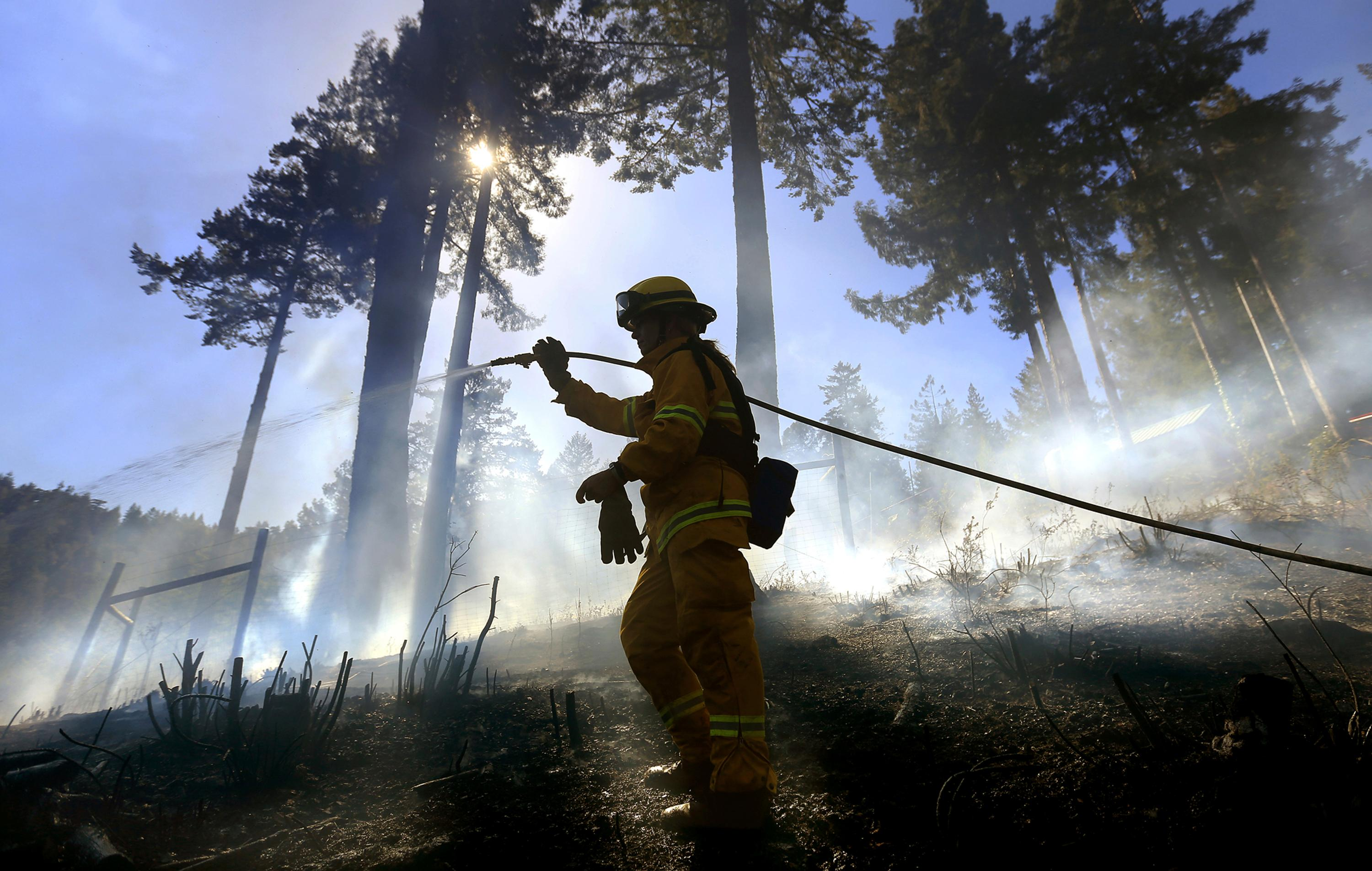"FILE - In this April 10, 2015 file photo, Monte Rio volunteer firefighter Gabriela Gibson sprays down hot spots on a half-acre fire in timber above Monte Rio, Calif., after a controlled burn crossed containment lines and wind blew embers in to the timber.  California's seemingly endless cycle of wildfires is helping drive plans to do more ""controlled burns"" that thin forests choked with dead trees and withered underbrush that if left unchecked can feed monster blazes that force entire communities to flee, destroy homes and take lives. The goal for 2018 is to burn at least 20,000 acres and to clear another 20,000 by crews using chain saws, bulldozers and other machinery. (Kent Porter/Santa Rosa Press Democrat via AP, File)"