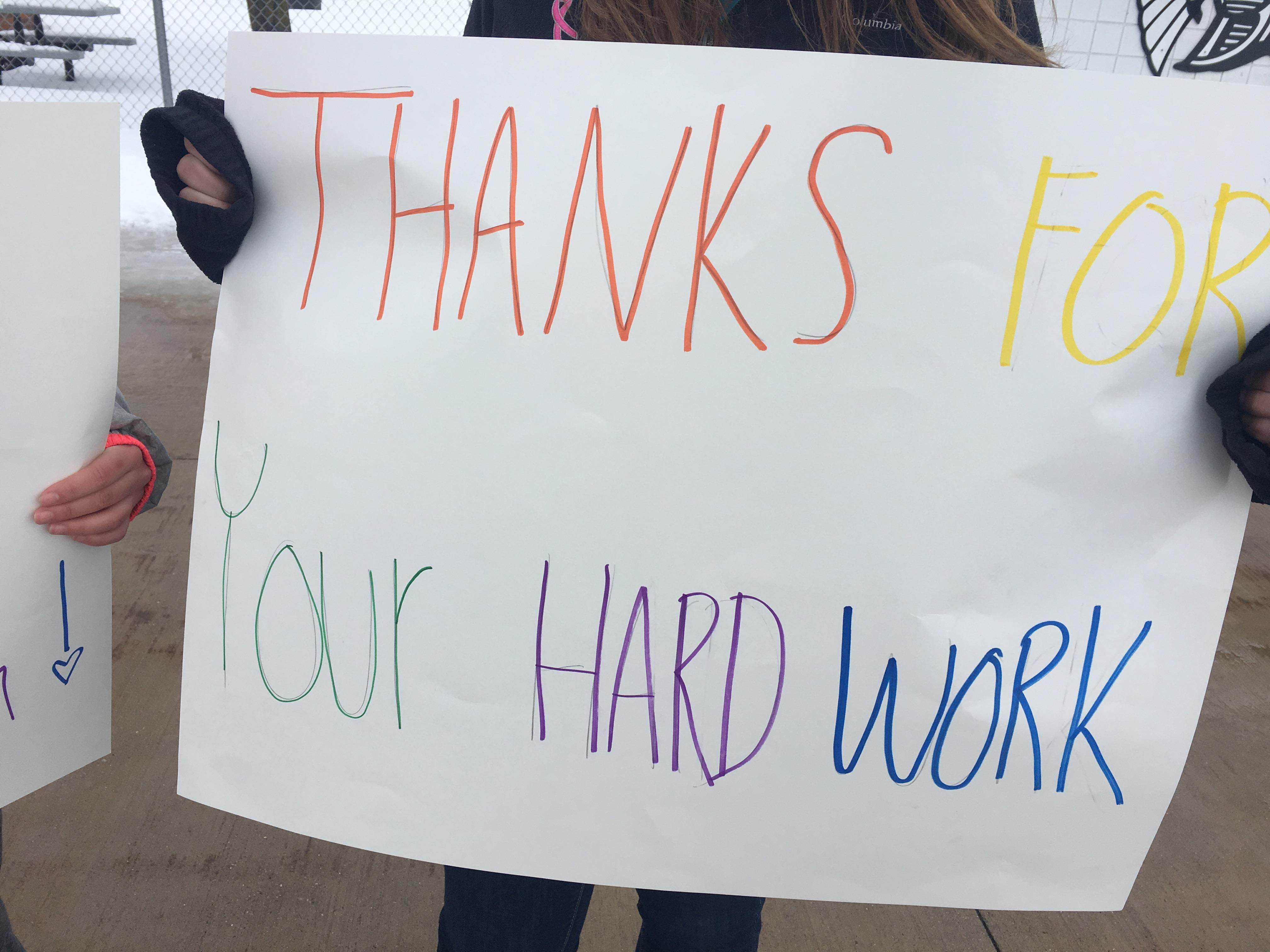 A sign held up by a Thornapple Kellogg High School student as they handed out treats to service workers and first responders.{ } (WWMT/Jason Heeres)