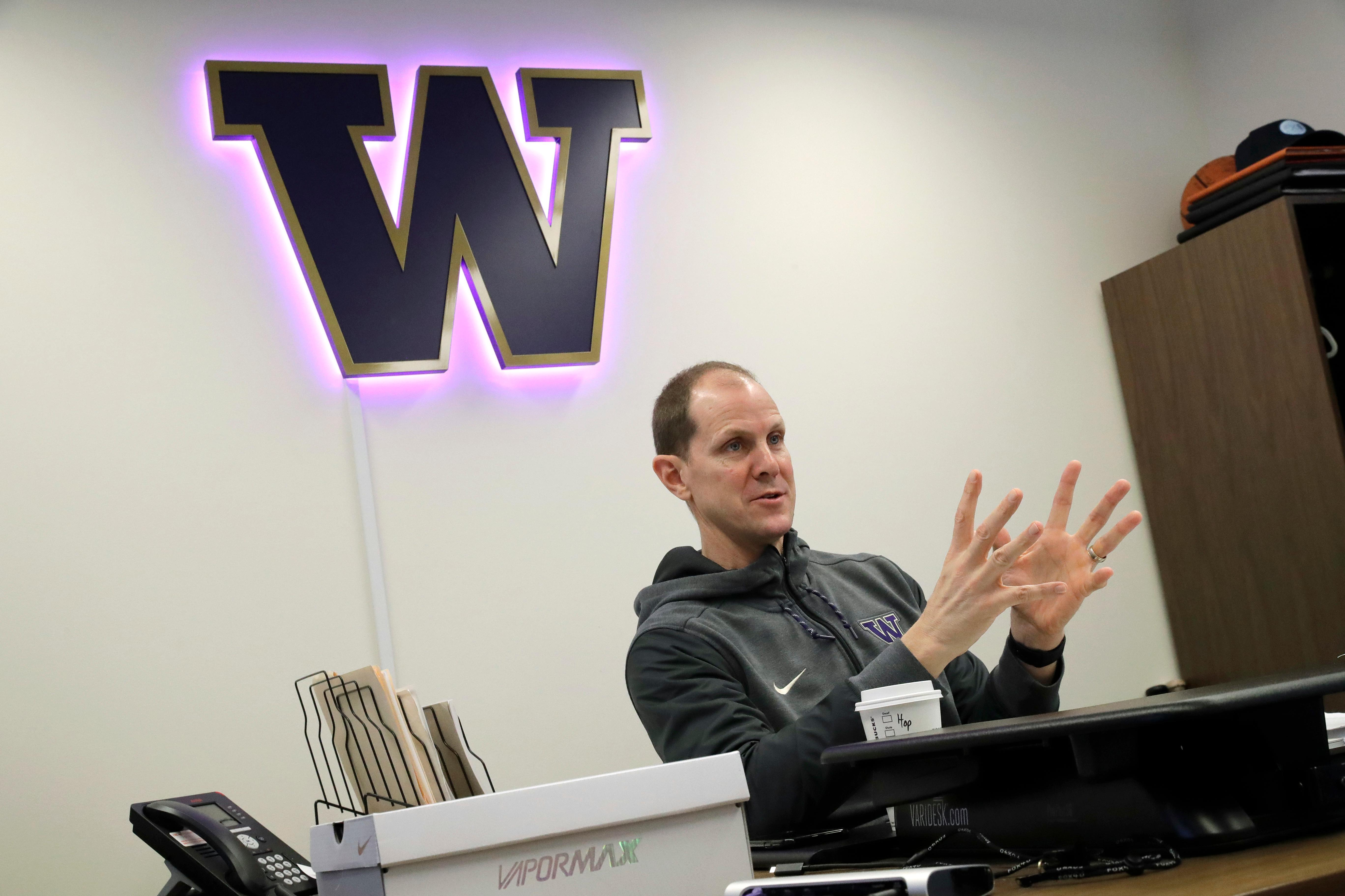 In this Sunday, Jan. 28, 2018 photo, Washington head coach Mike Hopkins sits in his office during a meeting with TV broadcasters before an NCAA college basketball game against Washington State in Seattle. One of the most surprising stories in college basketball is what Hopkins is doing in his first season at Washington and how the Huskies are in the conversation for an NCAA bid entering February. (AP Photo/Ted S. Warren)