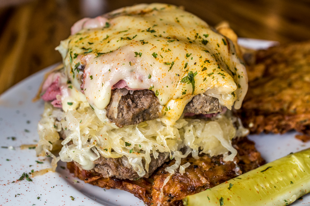 German Burger: grilled Angus beef on two haus-made potato pancakes topped with corned beef, sauerkraut, and Swiss cheese served with fries / Image: Catherine Viox // Published: 8.10.20