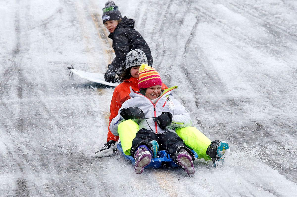 Children sled down a city street closed to traffic during a winter storm moving through the area, Monday, Feb. 6, 2017, in Seattle. Seattle finally got its dose of winter weather, with an overnight storm that left snow totals of an inch to more than a foot across western Washington, causing widespread school closures Monday. (AP Photo/Elaine Thompson)