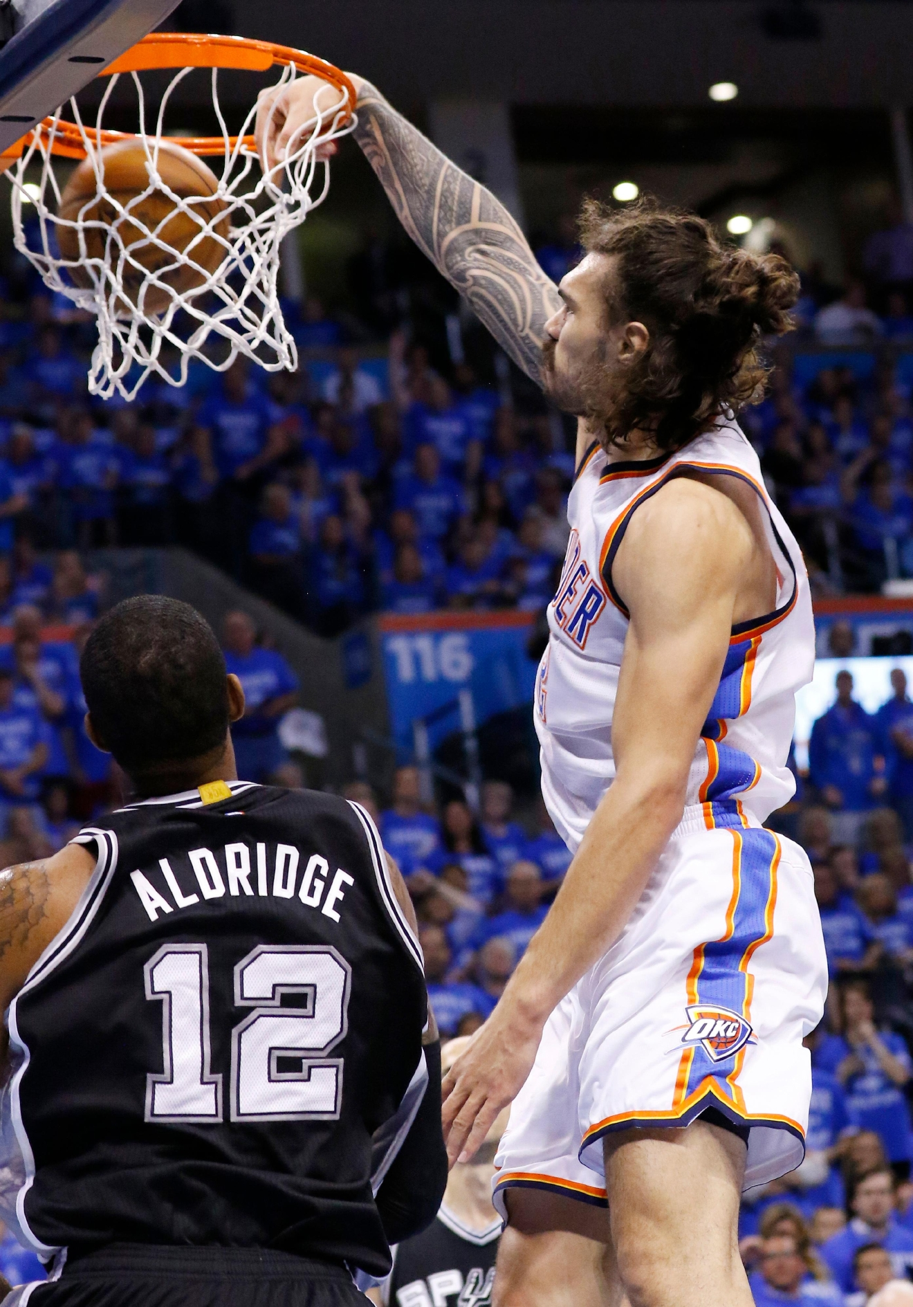 Oklahoma City Thunder center Steven Adams, right, dunks in front of San Antonio Spurs forward LaMarcus Aldridge (12) in the first quarter of Game 6 of a second-round NBA basketball playoff series in Oklahoma City, Thursday, May 12, 2016. (AP Photo/Alonzo Adams)
