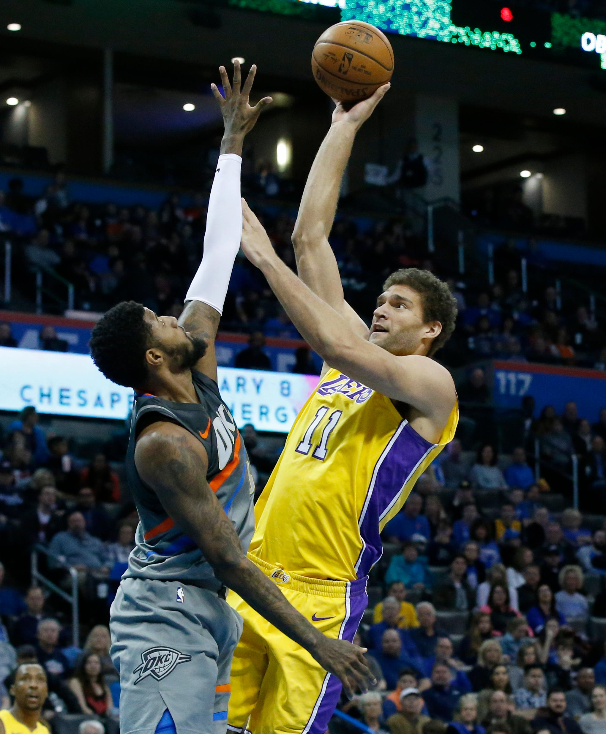 Los Angeles Lakers center Brook Lopez (11) shoots as Oklahoma City Thunder forward Paul George, left, defends in the first half of an NBA basketball game in Oklahoma City, Sunday, Feb. 4, 2018. (AP Photo/Sue Ogrocki)