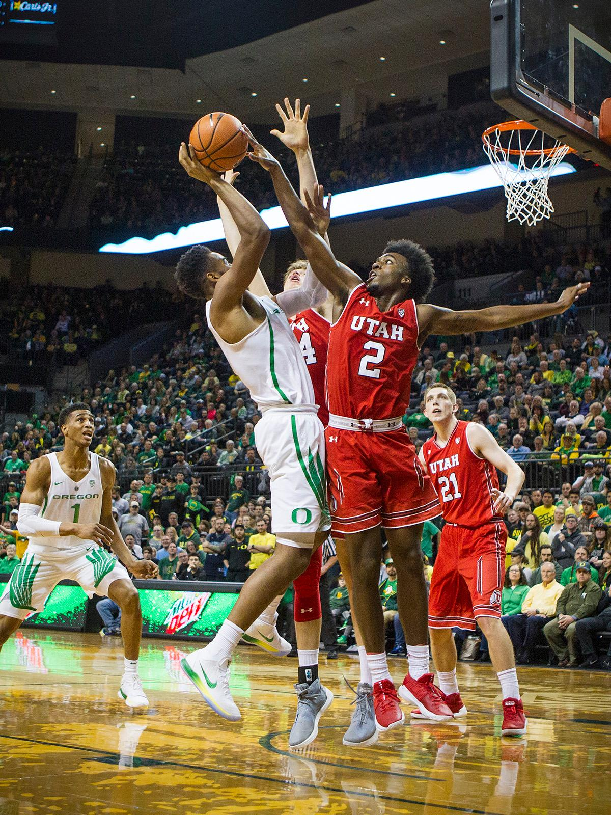 Oregon Ducks Troy Brown (#0) looks for the basket but is answered by Utah Utes Kolbe Caldwell (#2). The Utah Utes defeated the Oregon Ducks 66-56 on Friday night at Matthew Knight Arena. This is the first Pac-12 conference game loss at home for the Ducks since January of 2015. This also ended the five home game winning streak for the Ducks against the Utah Utes. Photo by Rhianna Gelhart, Oregon News Lab