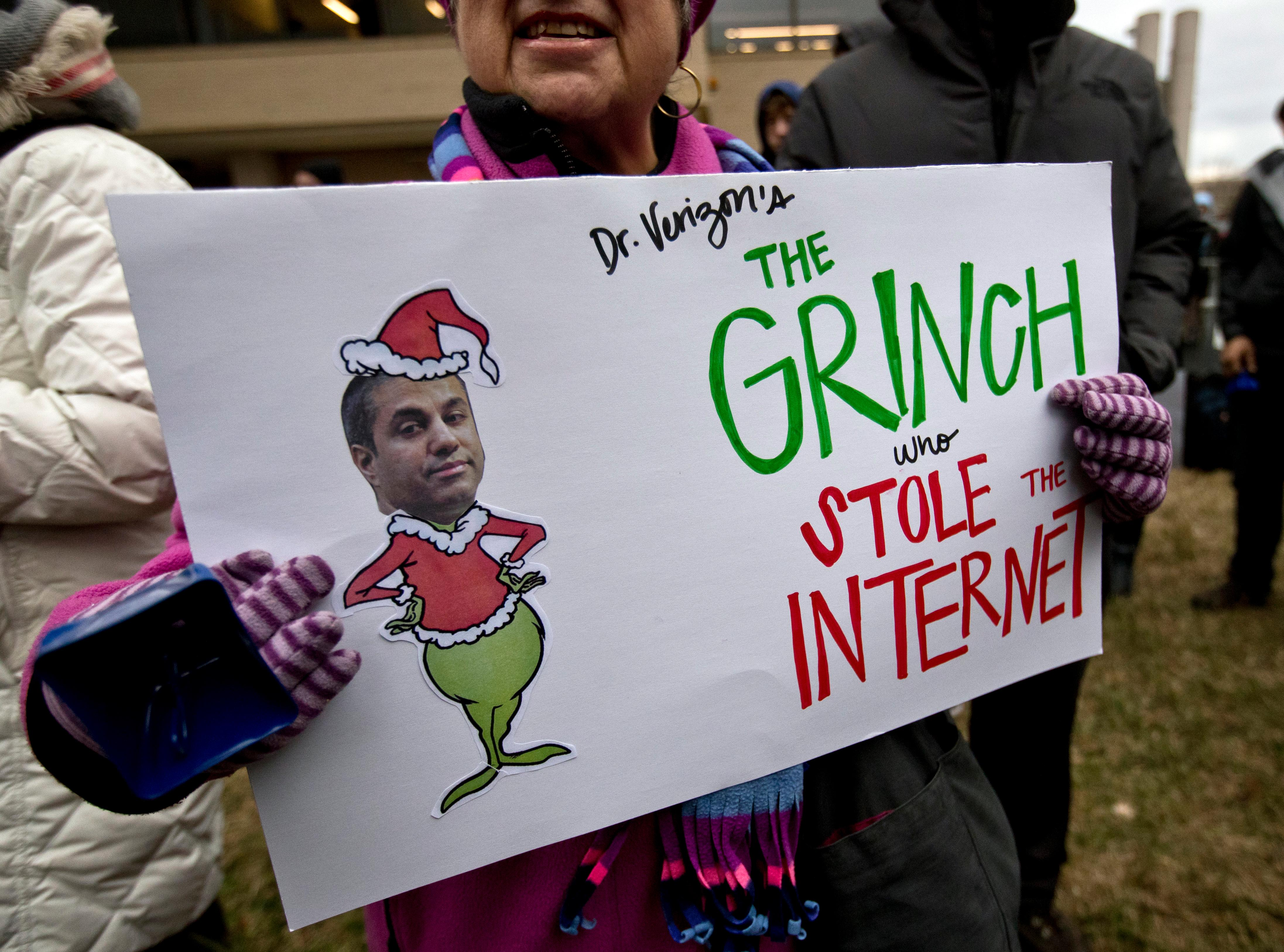 "Diane Tepfer holds a sign with an image of Federal Communications Commission (FCC) Chairman Ajit Pai as the ""Grinch who Stole the Internet"" as she protests near the FCC, in Washington, Thursday, Dec. 14, 2017, where the FCC is scheduled to meet and vote on net neutrality. The vote scheduled today at the FCC, could usher in big changes in how Americans use the internet, a radical departure from more than a decade of federal oversight. (AP Photo/Carolyn Kaster)"