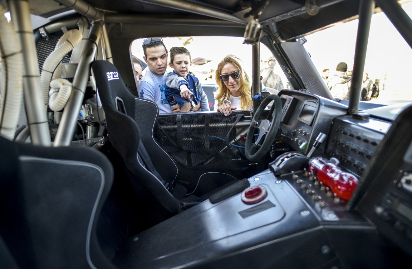 A family checks out the interior of one of the racers parked along Fremont Street East in Las Vegas as the Mint 400 4 Wheel Parts Vehicle Procession powered by Odyssey Battery kicks off the Mint 400 off-road race weekend on Wednesday, Mar. 1, 2017. [Mark Damon/Las Vegas News Bureau]