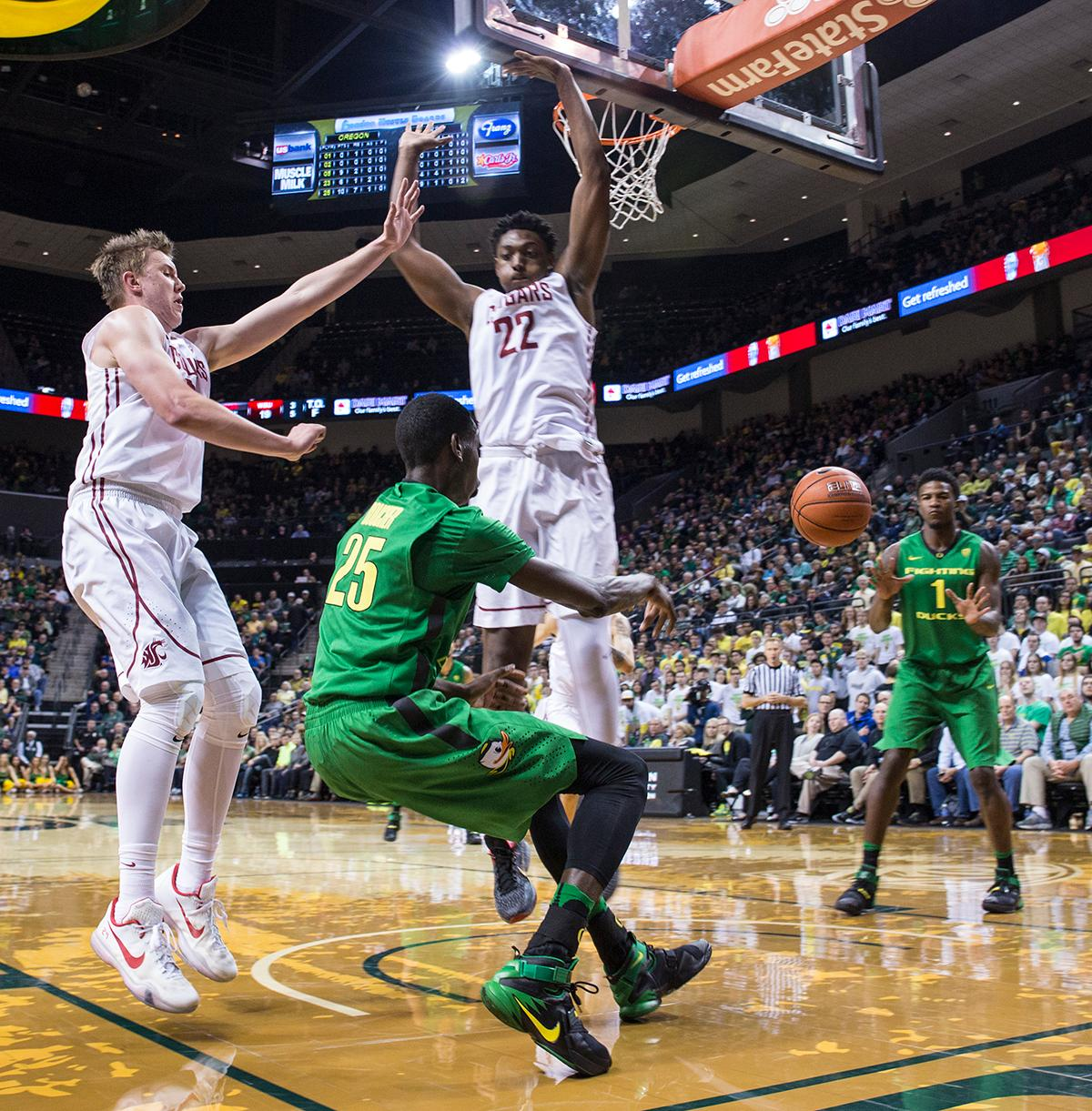 Oregon Ducks' Chris Boucher (#25) passes the ball to Jordan Bell (#1), while Washington State Cougars' Josh Hawkinson (#24) and Robert Franks (#22) defend against them. The Ducks beat the Cougars 76-62. Kianna Cabuco, Oregon News Lab