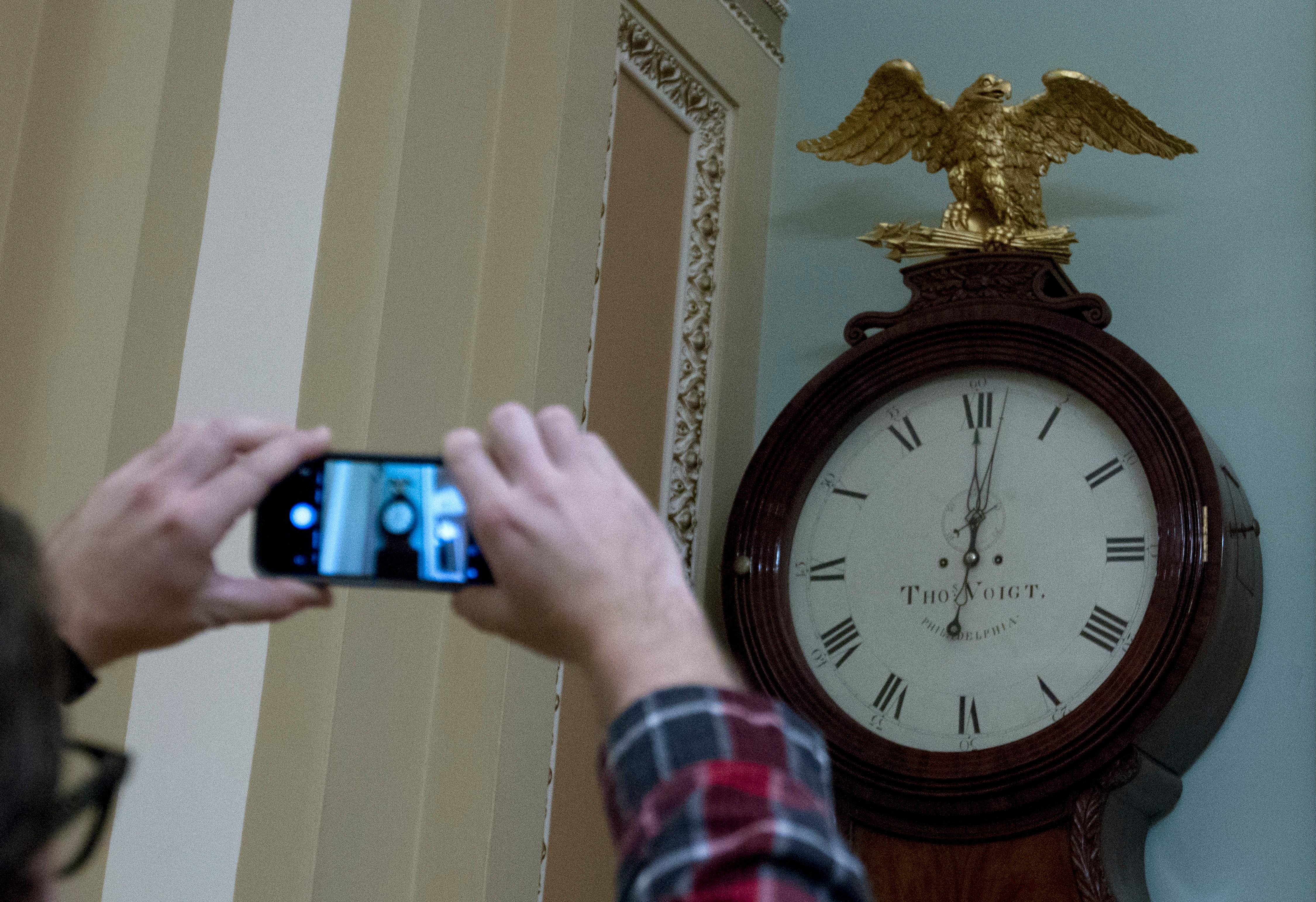 Photographers take a picture of the Ohio Clock shortly after midnight early Friday, Feb. 9, 2018, outside the Senate chamber at the Capitol, in Washington. (AP Photo/Jose Luis Magana)