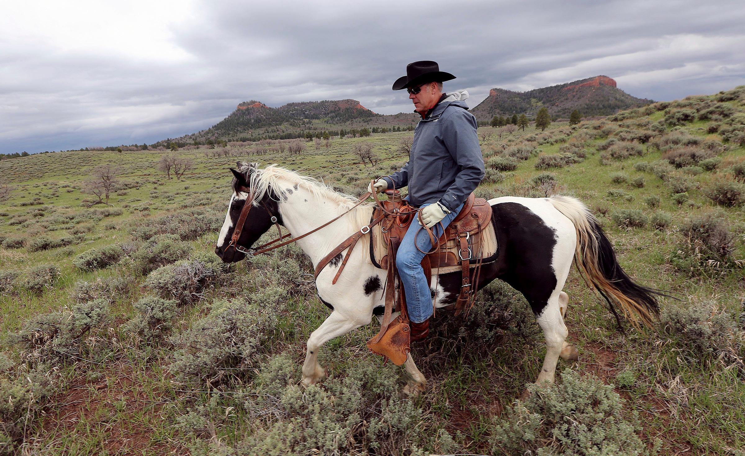 FILE - In this May 9, 2017, file photo, Interior Secretary Ryan Zinke rides a horse in the new Bears Ears National Monument near Blanding, Utah. Much of Bears Ears is on land administered by the Bureau of Land Management, which is part of Zinke's department. Western lawmakers are arguing that BLM headquarters should be moved from Washington, D.C., to the West because of its influence there. (Scott G Winterton/The Deseret News via AP, File)