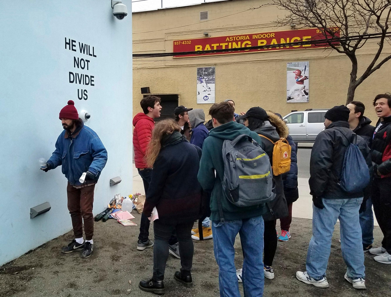 "Actor Shia LeBeouf, left, stands in front of a live-steam camera with the words ""HE WILL NOT DIVIDE US"" posted on a wall outside of the the Museum of the Moving Image as members of the public join LeBeouf in chanting the words ""He will Not Divide Us"" in the Queens borough of New York. LaBeouf has spent the first four days of the Trump presidency swaying, dancing and chanting, along with anyone who wants to join in. The project by LeBeouf and two other artists opened on Jan. 20 and is expected to go for 4 years, or for ""the duration of the presidency."" (AP Photo/Deepti Hajela)"