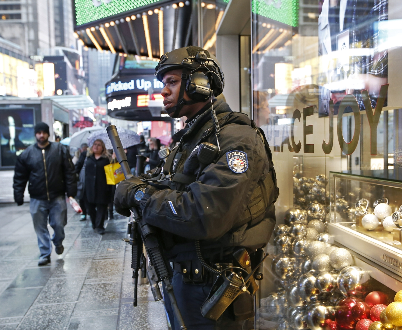 A heavily armed counterterrorism officer takes shelter beneath an overhang above a store in Times Square, Thursday, Dec. 29, 2016, in New York. The city's police are once again saying they are up to the task of protecting the huge crowds that are expected to gather in and around Times Square for New York City's massive New Year's Eve celebration. (AP Photo/Kathy Willens)