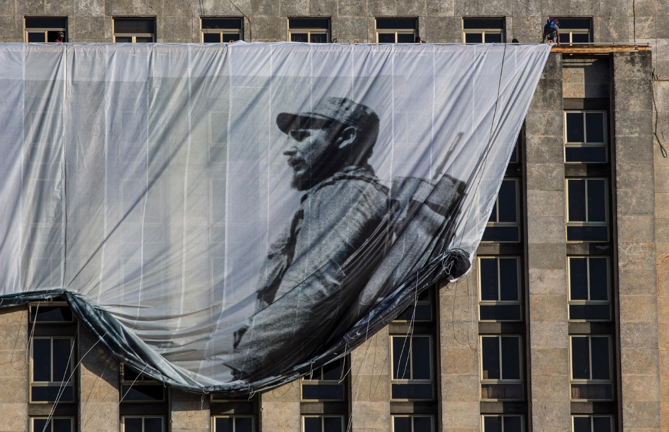 Men hang a giant banner with a picture of Cuba's late leader Fidel Castro as a young revolutionary, from the Cuban National Library building in Havana, Cuba, Sunday, Nov. 27, 2016.  (AP Photo/Desmond Boylan)