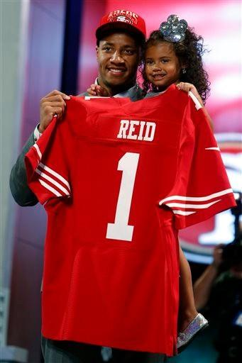Eric Reid, from Louisiana State, holds up a team jersey and his daughter after being selected 18th overall by the San Francisco 49ers in the first round of the NFL football draft, Thursday night.