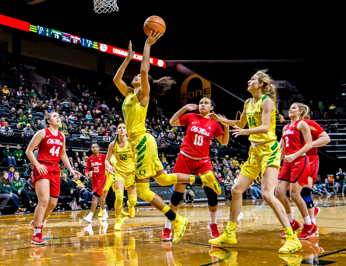 The Duck's Satou Sabally (#0) runs the ball in for a shot. The Duck's Sabrina Ionescu (#20) is introduced at the start of the game against the Ole Miss Rebels. The Oregon Ducks womens basketball team defeated the Ole Miss Rebels 90-46 on Sunday at Matthew Knight Arena. Sabrina Ionescu tied the NCAA record for triple-doubles, finishing the game with 21 points, 14 assists, and 11 rebounds. Ruthy Hebard added 16 points, Satou Sabally added 12, and both Lexi Bando and Maite Cazorla scored 10 each. The Ducks will next face off against Texas A&M on Thursday Dec. 21 and Hawaii on Friday Dec. 22 in Las Vegas for Duel in the Desert before the start of Pac-12 games. Photo by August Frank, Oregon News Lab
