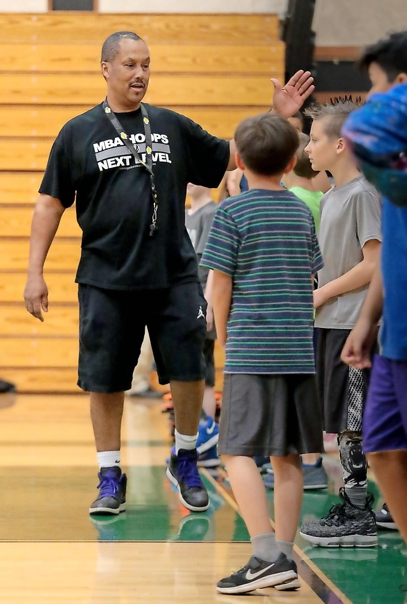 Manny Crump works with kids during an MBA Hoops session at the Central High gym in Medford.