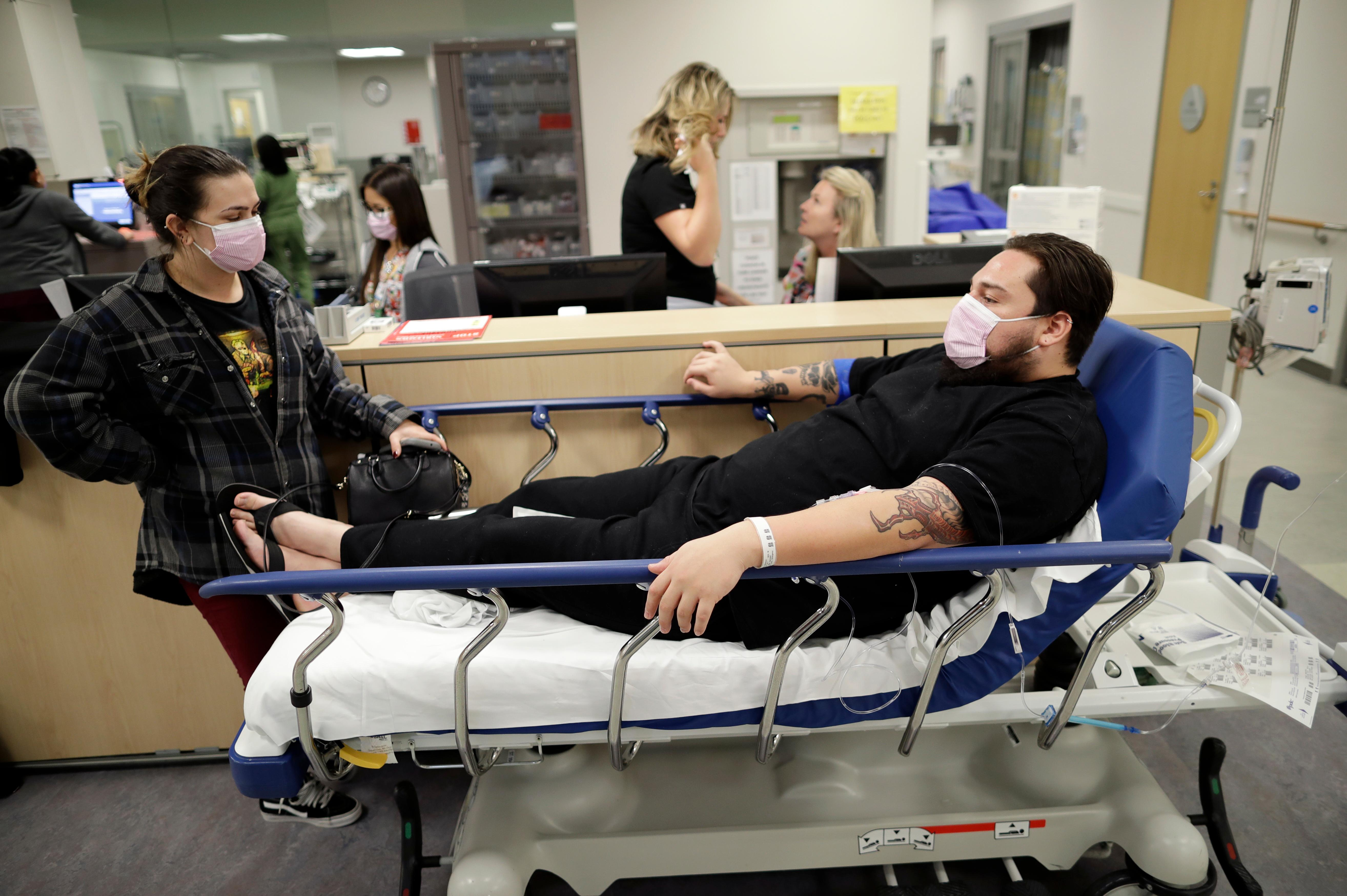 Donnie Cardenas, right, waits in an emergency room hallway alongside roommate Torrey Jewett, left, as he recovers from the flu at the Palomar Medical Center in Escondido, Calif., on Wednesday, Jan. 10, 2018. The San Diego County resident said he was battling a heavy cough for days before a spike his temperature sent him into the emergency room. (AP Photo/Gregory Bull)