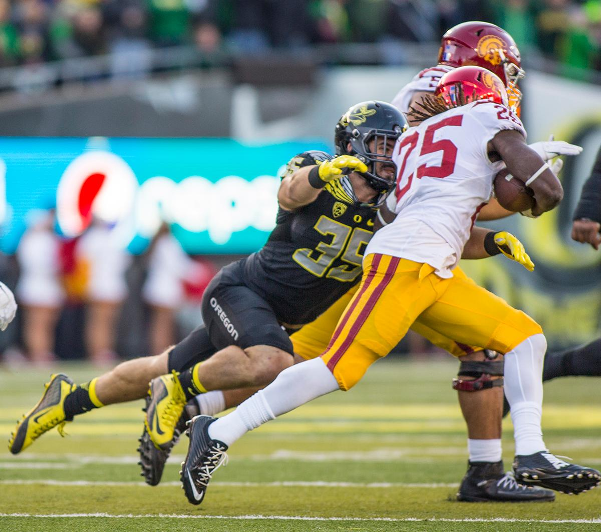 Oregon Ducks' linebacker, Joe Walker (#35) lunges after USC Trojans' tail back, Ronald Jones II (#25). The Ducks beat the Trojans 48-28. Kianna Cabuco, Oregon News Lab