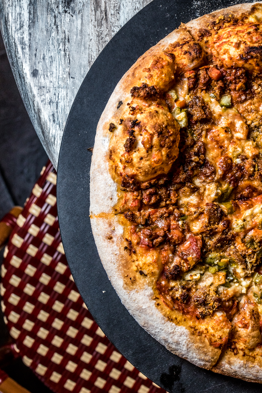 Rick's Spicy Sausage Pizza topped with bolognese sauce, parmesan and fontinella cheese, house-made sausage, and pepper relish / Image: Catherine Viox // Published: 4.21.20