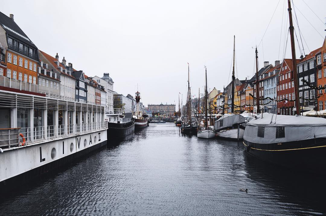 "IMAGE: IG user @themvmtblog / POST: This is #Nyhavn, or the ""painted houses,"" the most beautiful area of #Copenhagen. We love looking down the canal and seeing the boats and houses on both sides. The buildings that line the canal are mostly bars and restaurants, so it's easy to grab a quick bite or drink when you're in this area. Even though it was pretty cold when we were there in mid-November, plenty of people still sat outside along the canal with blankets provided by the restaurants. Could you see yourself spending an afternoon relaxing here? // PUBLISHED: 10.29.16"