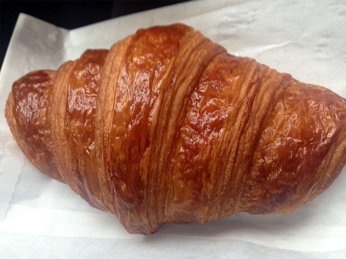 The golden exterior of this croissant will end up in your lap, but it's completely worth it. (Image: Jenny Kuglin / Seattle Refined)
