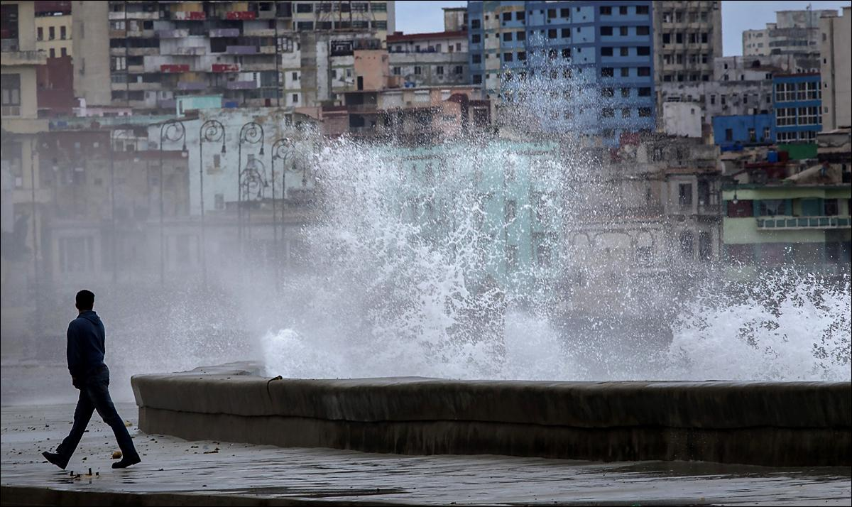A man walks away from the breaking waves during a cold front, on Havana's malecon, in Cuba, Monday, Jan. 18, 2016. (AP Photo/Ramon Espinosa)