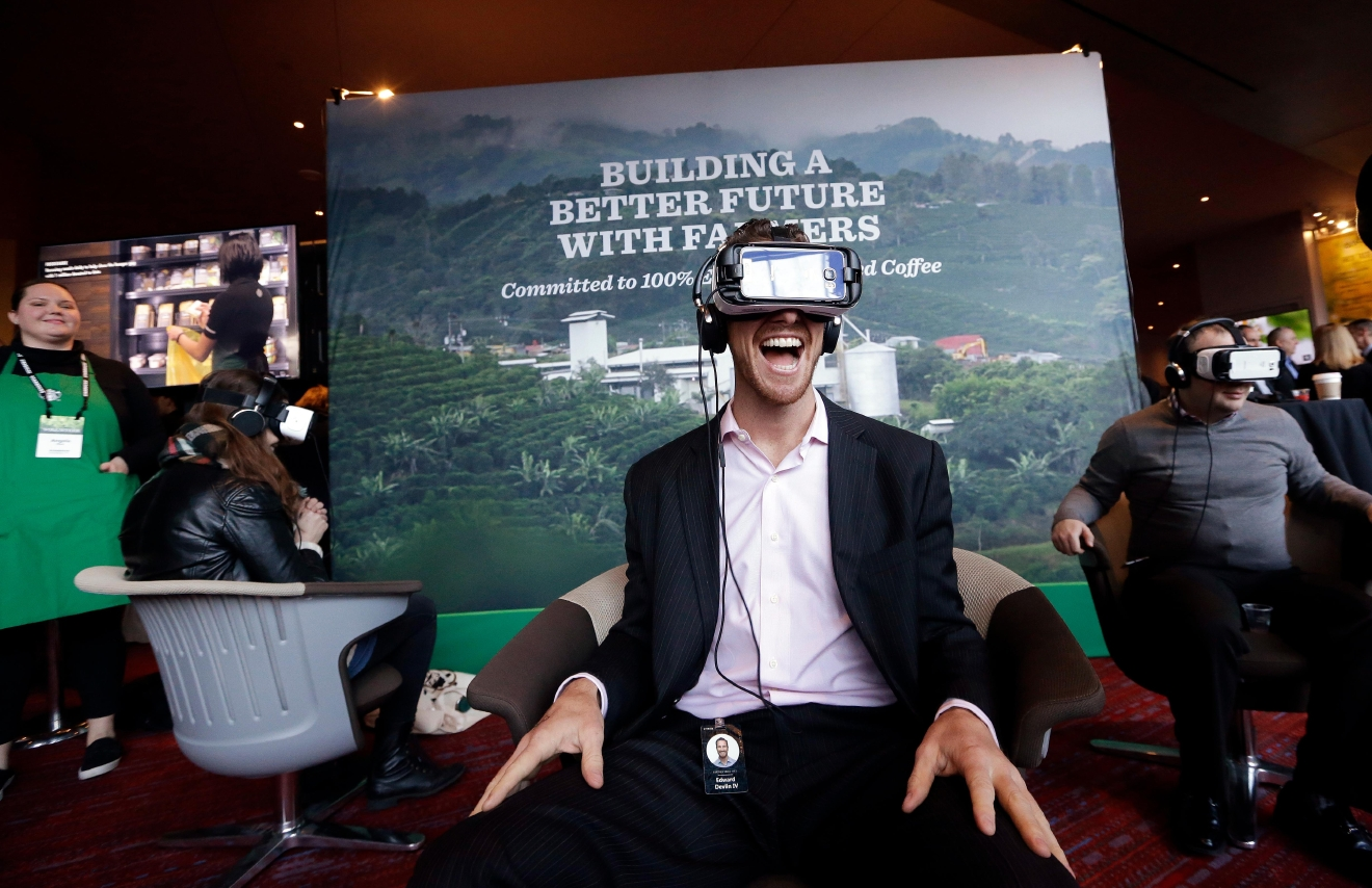 Starbucks employee Ed Devlin reacts as he views a 360 video of a Starbucks' Costa Rica coffee farm at a display before the company's annual shareholder meeting, Wednesday, March 22, 2017, in Seattle. (AP Photo/Elaine Thompson)