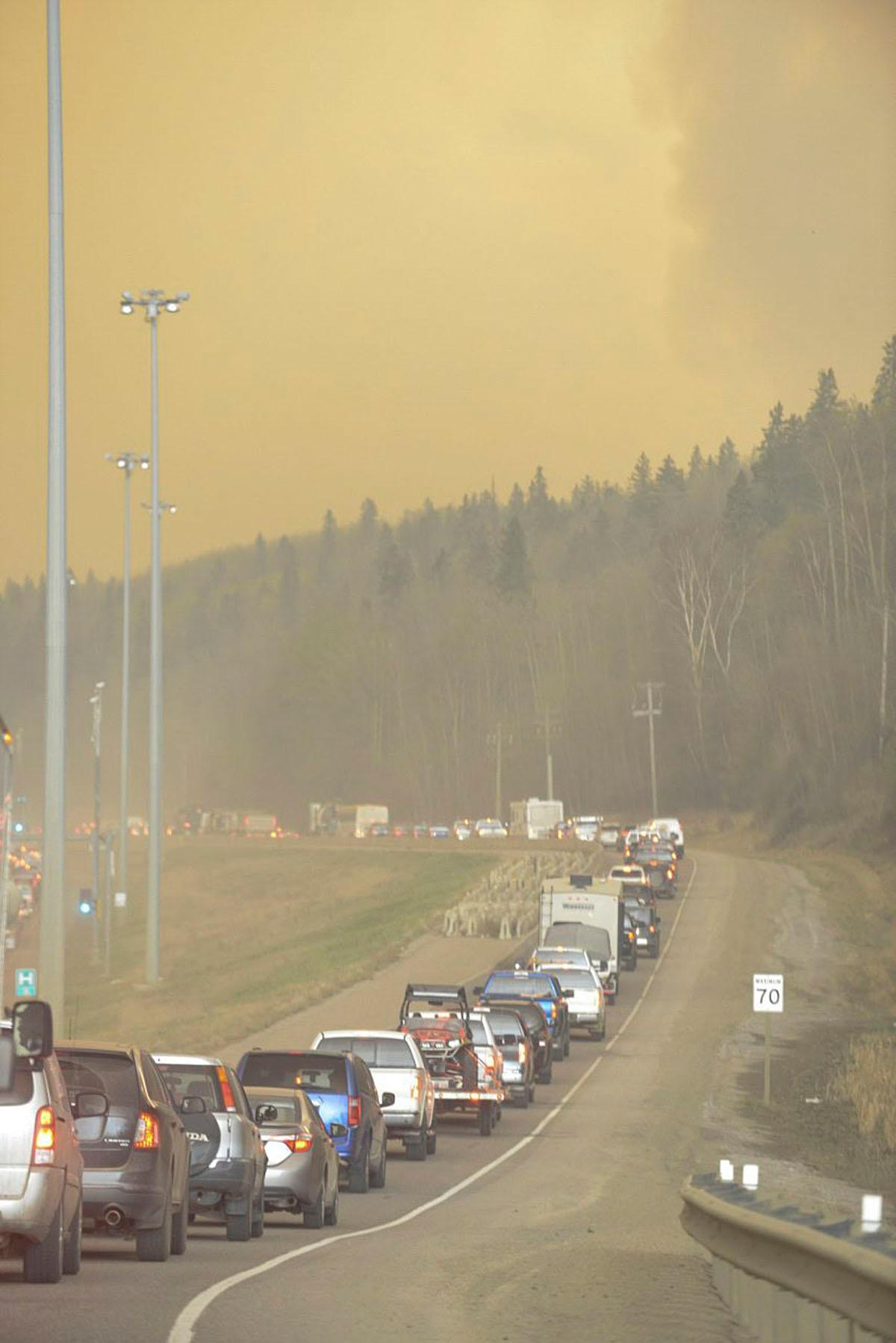 Smoke fills the air as people drive on a road in Fort McMurray, Alberta, Tuesday, May 3, 2016. At least half of a northern Alberta city was ordered evacuated Tuesday as a wildfire whipped by winds engulfed homes and sent ash raining down on residents. (Greg Halinda/The Canadian Press via AP) MANDATORY CREDIT