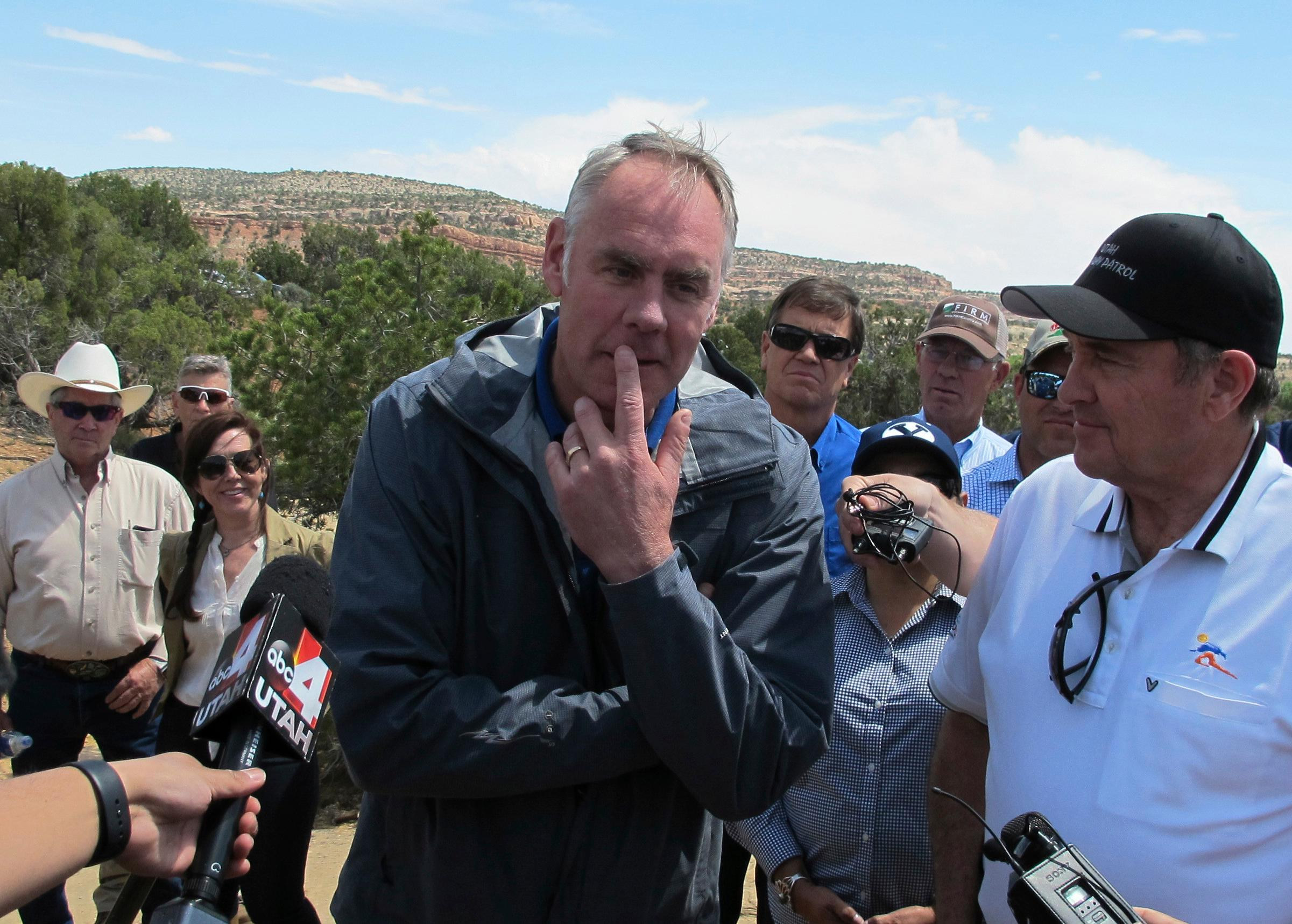 Interior Secretary Ryan Zinke, center, is joined by Utah Gov. Gary Herbert, right, during a press conference Monday, May 8, 2017, at the Butler Wash trailhead within Bears Ears National Monument near Blanding, Utah. Zinke says he wants to make sure Native American cultural standing is preserved in a new national monument but cautioned that not all tribal members share the same opinion about it. (AP Photo/Michelle Price)