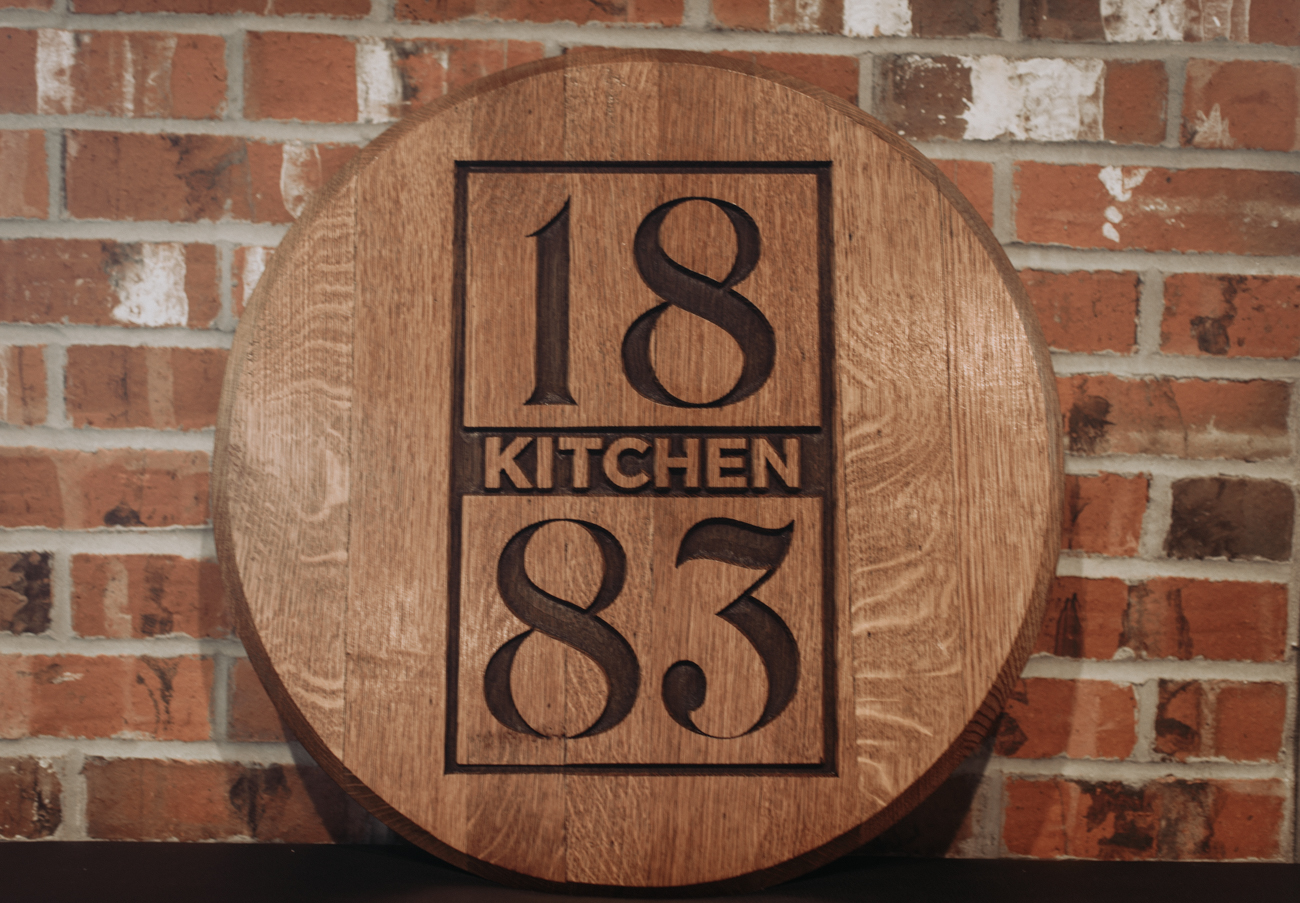 "Kitchen 1883 describes itself as ""new American comfort food."" Located in Union, Kentucky, the restaurant is a Kroger-owned concept that opened in November of 2017. The wood-walled eatery is directly attached to the Union Kroger store and is accessible from the sidewalk. Leather booths, Edison bulbs, and tasteful rustic decor are as much a feast for the eyes as the expansive menu is for diners. In addition to fresh comfort food, bourbon and cocktails are available at the bar. ADDRESS: 9003 US Highway 42 (41091) / Image: Brianna Long // Published: 5.17.18"