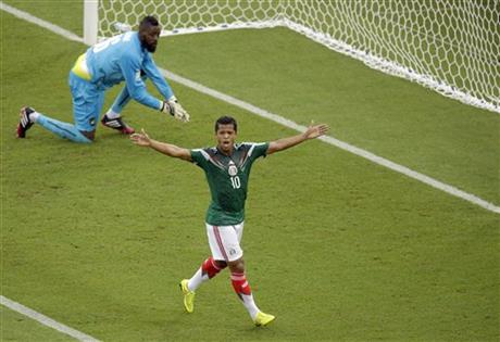 Mexico's Giovani dos Santos, right, reacts after a goal was disallowed while Cameroon's goalkeeper Charles Itandje looks on during the group A World Cup soccer match between Mexico & Cameroon in the Arena das Dunas in Natal, Brazil, Friday, June 13, 2014.