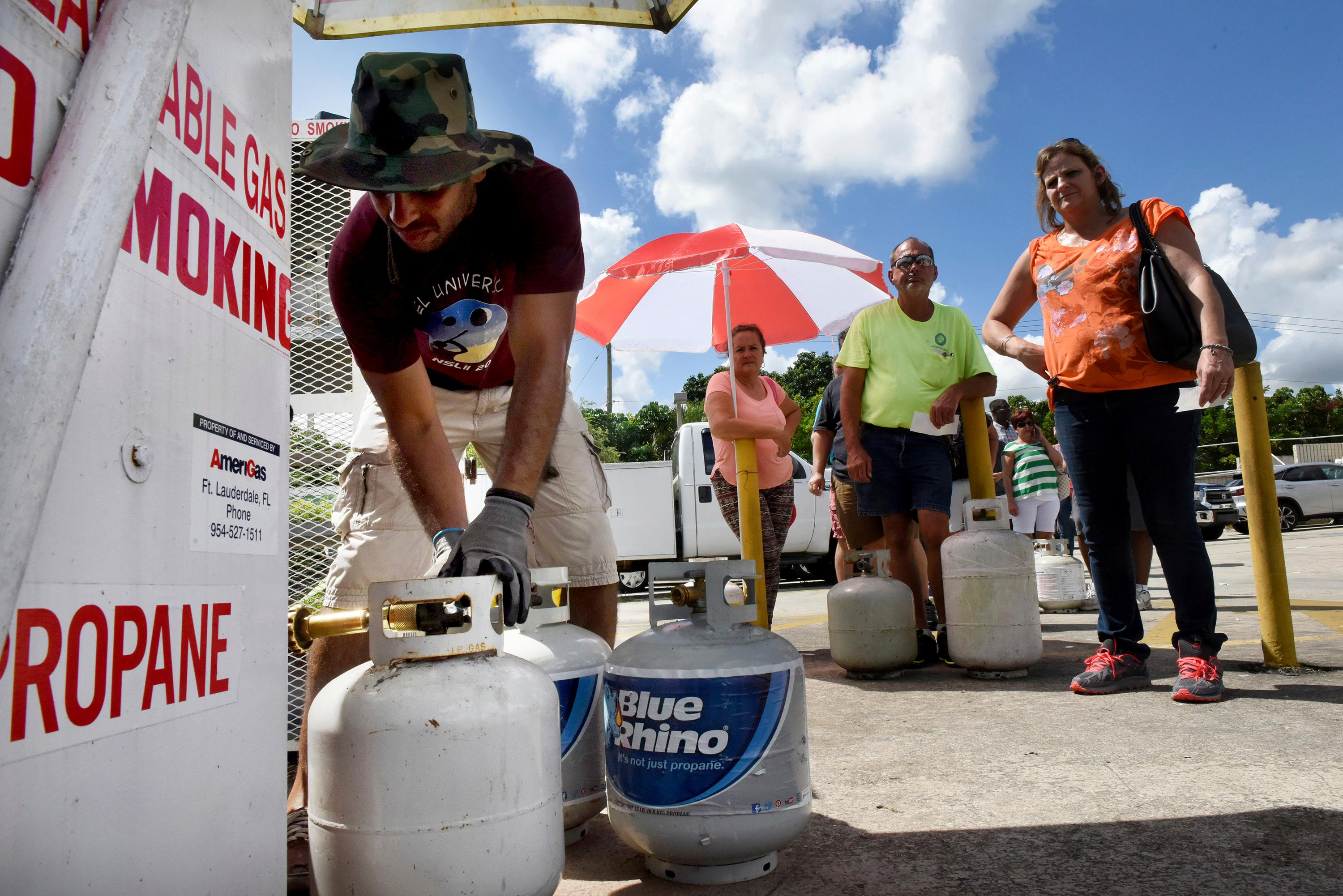 Gustavo Galindo, left, fills propane tanks at an Exxon gas station in Davie, Fla., Thursday, Sept. 7, 2017, as a long line of people wait in line as residents prepare for Hurricane Irma. (Taimy Alvarez/South Florida Sun-Sentinel via AP)