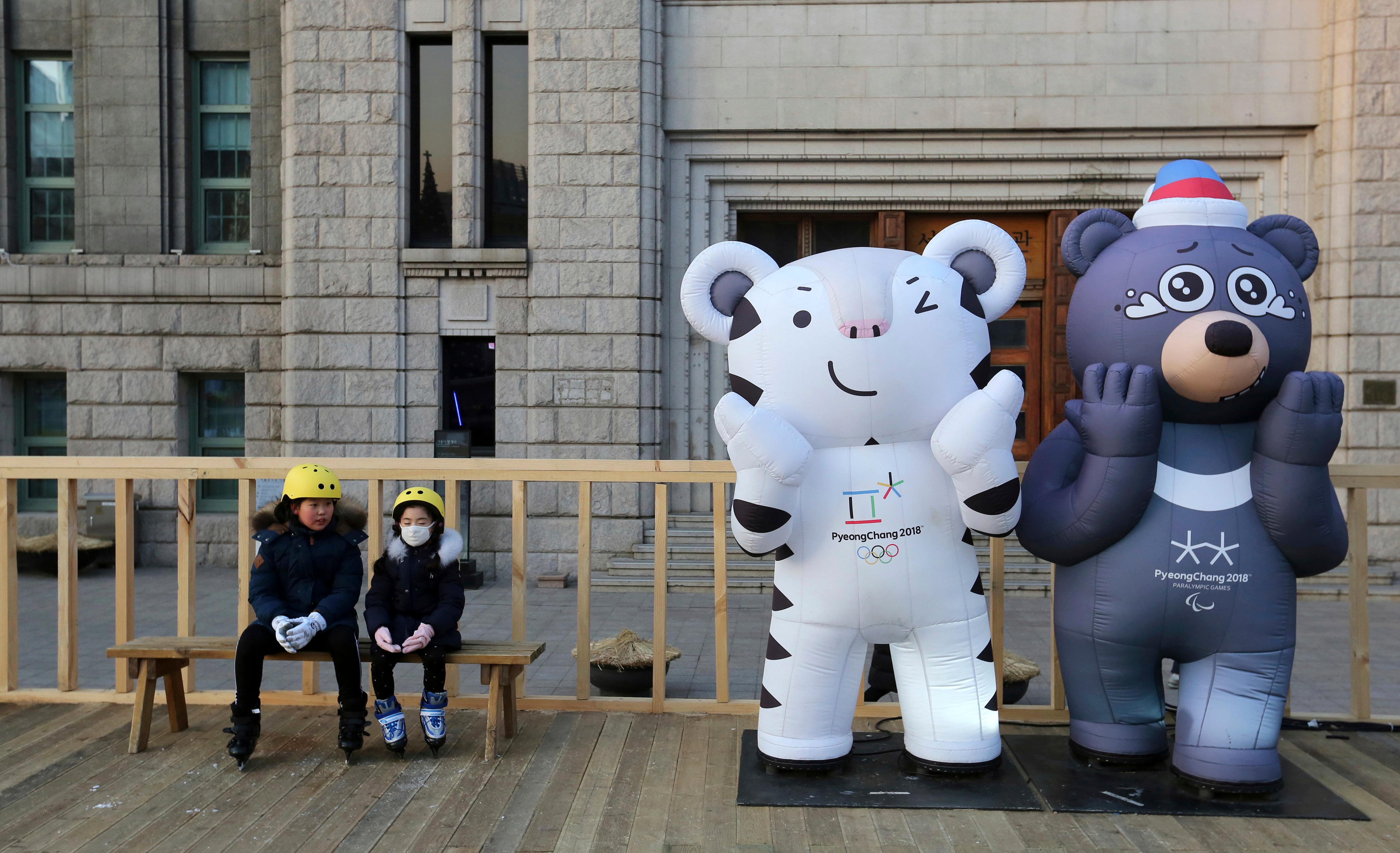 Children sit next to the 2018 Pyeongchang Winter Olympic Games' official mascots, a white tiger Soohorang, for the Olympics, and black bear Bandabi, right, for Paralympics, near Seoul Plaza Ice Rink in Seoul, South Korea, Tuesday, Jan. 2, 2018. South Korea on Tuesday offered high-level talks with rival North Korea to find ways to cooperate on next month's Winter Olympics in the South. (AP Photo/Ahn Young-joon)