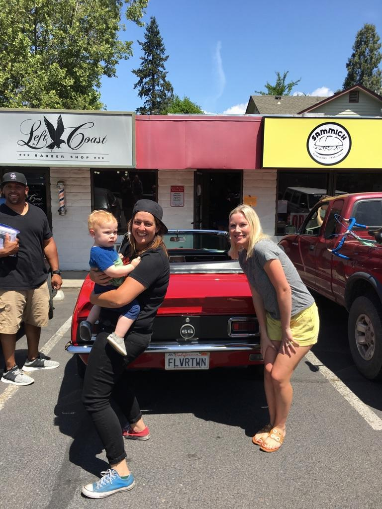 "<p>Photo courtesy of Sammich</p><p>Sammich chef and owner Melissa McMillan (with cap on backward) poses with others by celebrity chef Guy Fieri's 1967 Chevy Camaro SS Convertible with a ""FLVRTWN"" license plate.</p>"