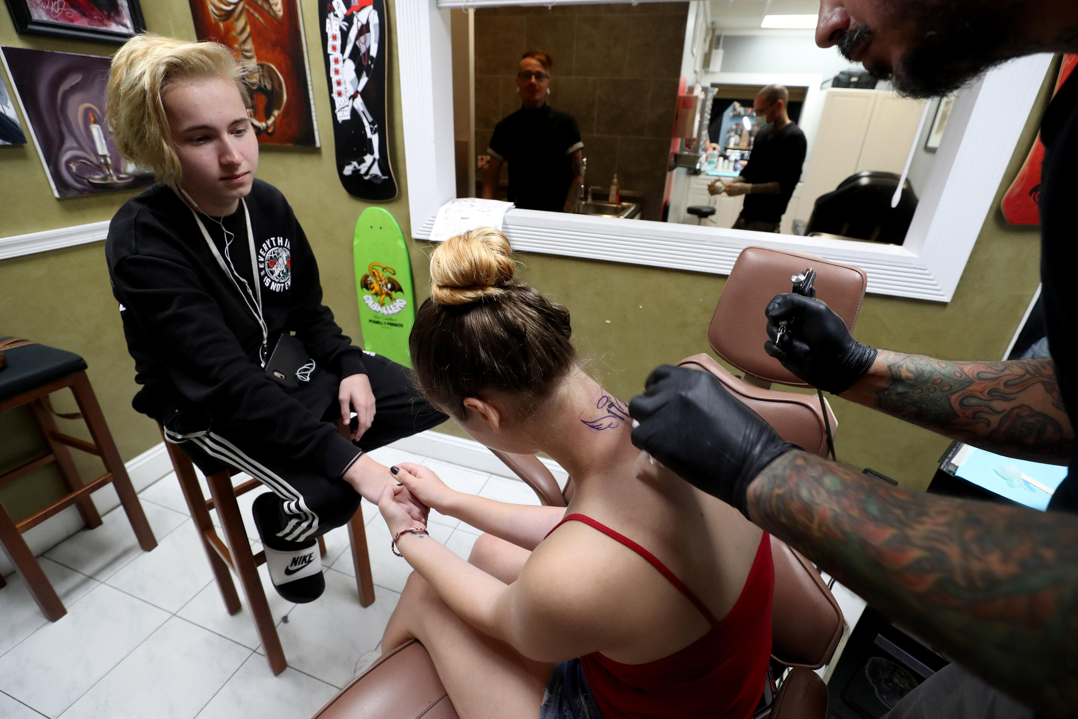 Justus Culver, 16, a Marjory Stoneman Douglas student, holds the hand of friend Rio Gonzales, 17, a Coral Springs High student, as she gets the number 17 and angel wings tattooed to the back of her neck by artist Ted Mendoza of No Hard Feelings Tattoo Gallery in Coral Springs.  The tattoo shop  along with nine other tattoo artists and body piercers, offered a day of free tattoos to the community with donations going toward the families and victims of the Marjory Stoneman Douglas shooting.{ }(Susan Stocker/South Florida Sun-Sentinel via AP)