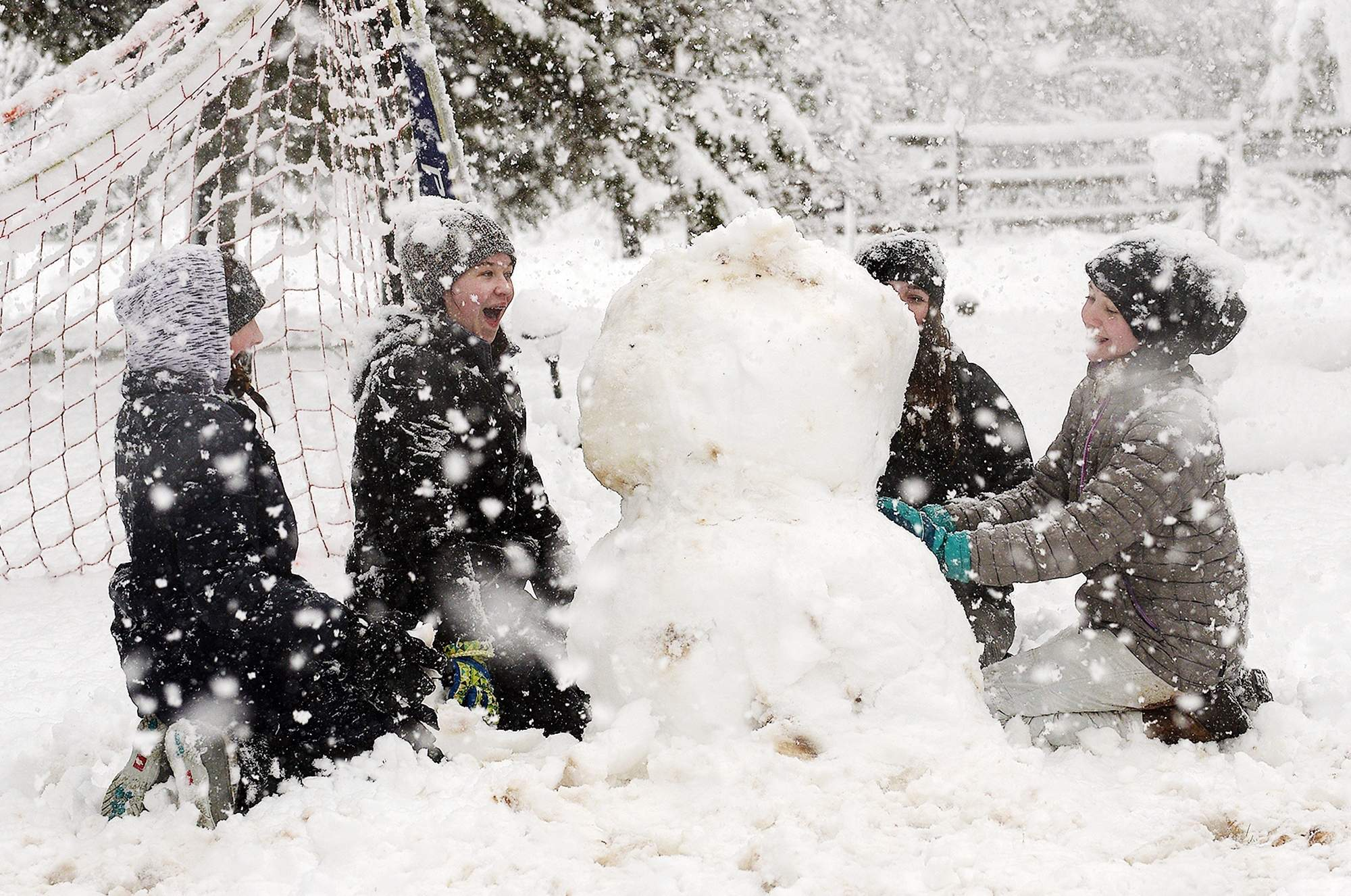From left, Ashley Allen, Georgia Kelso, Jordyn Fuges and Molly Kelso build a snowman during the nor'easter Wednesday, March 7, 2018, in New Britain Borough. [KIM WEIMER / STAFF PHOTOJOURNALIST]