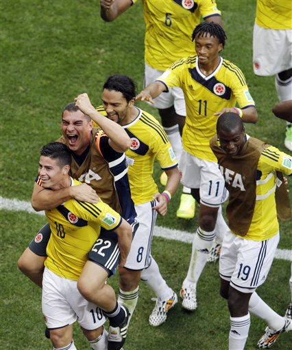 Colombia's James Rodriguez, left, celebrates with teammate goalkeeper Faryd Mondragon during the group C World Cup soccer match between Colombia and Ivory Coast at the Estadio Nacional in Brasilia, Brazil, Thursday, June 19, 2014.