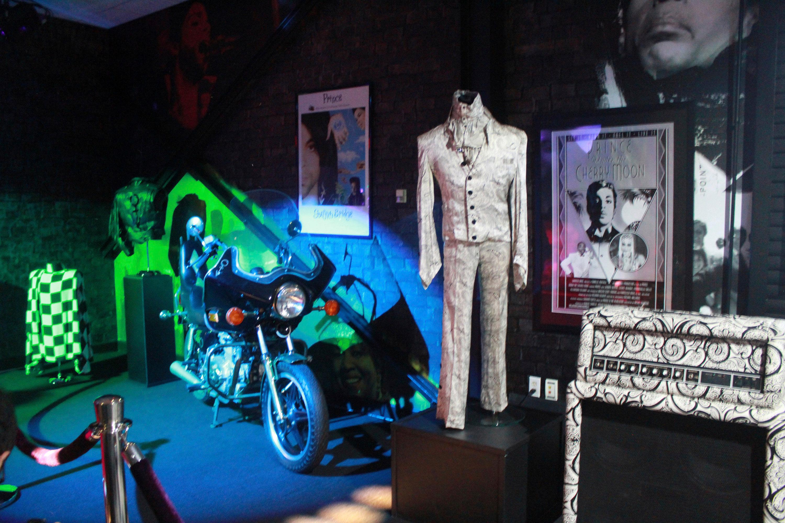 "FILE - In this Nov. 2, 2016 file photo, a Prince costume and motorcycle are on display at Prince's Paisley Park in Chanhassen, Minn. Paisley Park, home and studio of the late musician Prince, is open for public tours. At his home and recording studio-turned-museum, a full four days of events are on tap for the one-year anniversary of his death on April 21, 2016, ranging from concert performances by the great one's former band mates to panel discussions on his legacy. Fans who can't afford those high-dollar tickets can head to a street party outside the club he made famous in ""Purple Rain."" (AP Photo/Jeff Baenen, File)"