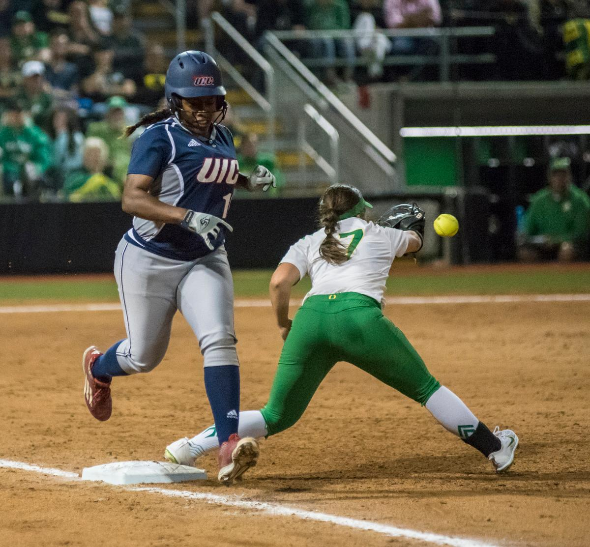 Chicago Flames player Tiana Mack-Miller (#10) safely runs to first as Oregon Ducks Mia Camuso (#7) attempts to catch the ball. The No. 3 Oregon Ducks defeated the University of Illinois Chicago Flames 13-0 with the run-rule on Saturday night at Jane Sanders Stadium. The Ducks scored in every inning and then scored nine runs at the bottom of the fourth. The Oregon Ducks are now 22-0 in NCAA regional games. The Oregon Ducks play Wisconsin next on Saturday, May 20 at 2pm at Jane Sanders Stadium. Photo by Cheyenne Thorpe, Oregon News Lab