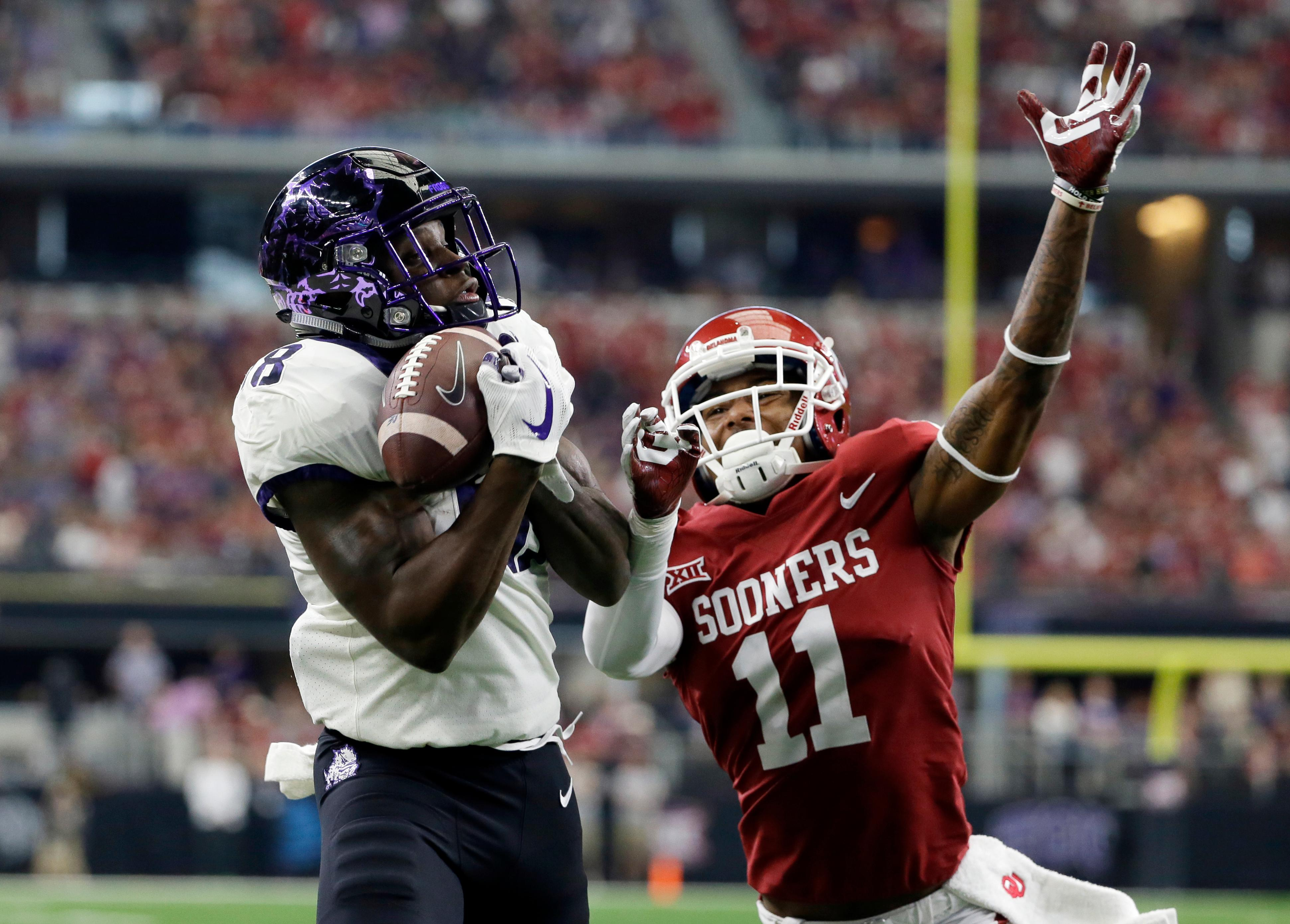 TCU wide receiver Jalen Reagor (18) catches a touchdown pass in front to Oklahoma cornerback Parnell Motley (11) in the first half of the Big 12 Conference championship NCAA college football game, Saturday, Dec. 2, 2017, in Arlington, Texas. (AP Photo/Tony Gutierrez)