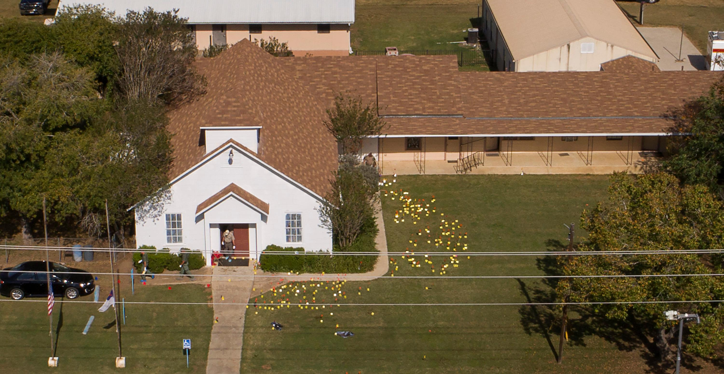 Flags mark evidence on the lawn of the First Baptist Church in Sutherland Springs, Texas, Monday, Nov. 6, 2017, a day after over 20 people died in a mass shooting Sunday. (Jay Janner/Austin American-Statesman via AP)