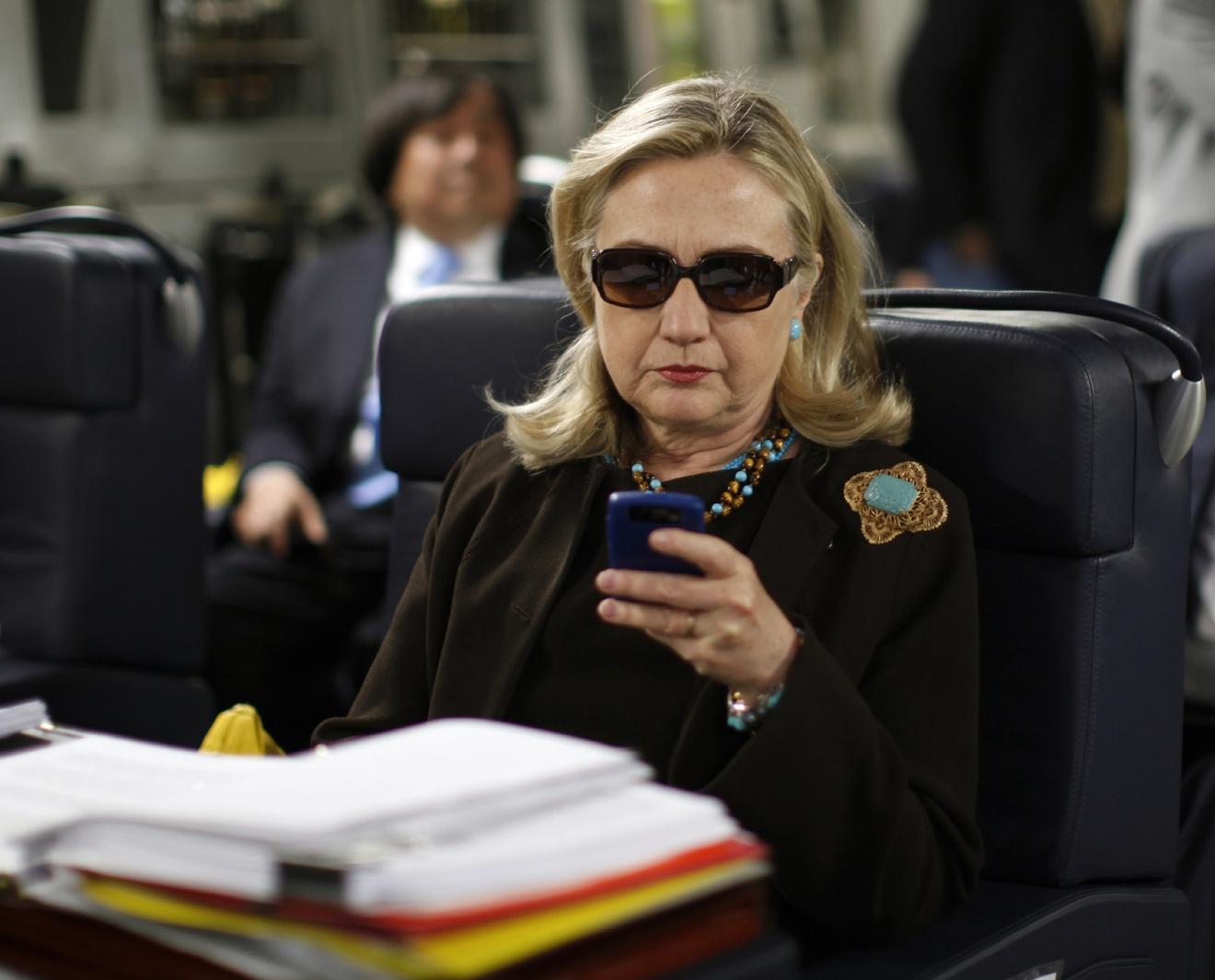 FILE - In this Oct. 18, 2011, file photo, then-Secretary of State Hillary Rodham Clinton checks her Blackberry from a desk inside a C-17 military plane upon her departure from Malta, in the Mediterranean Sea, bound for Tripoli, Libya. (AP Photo/Kevin Lamarque, Pool, File)