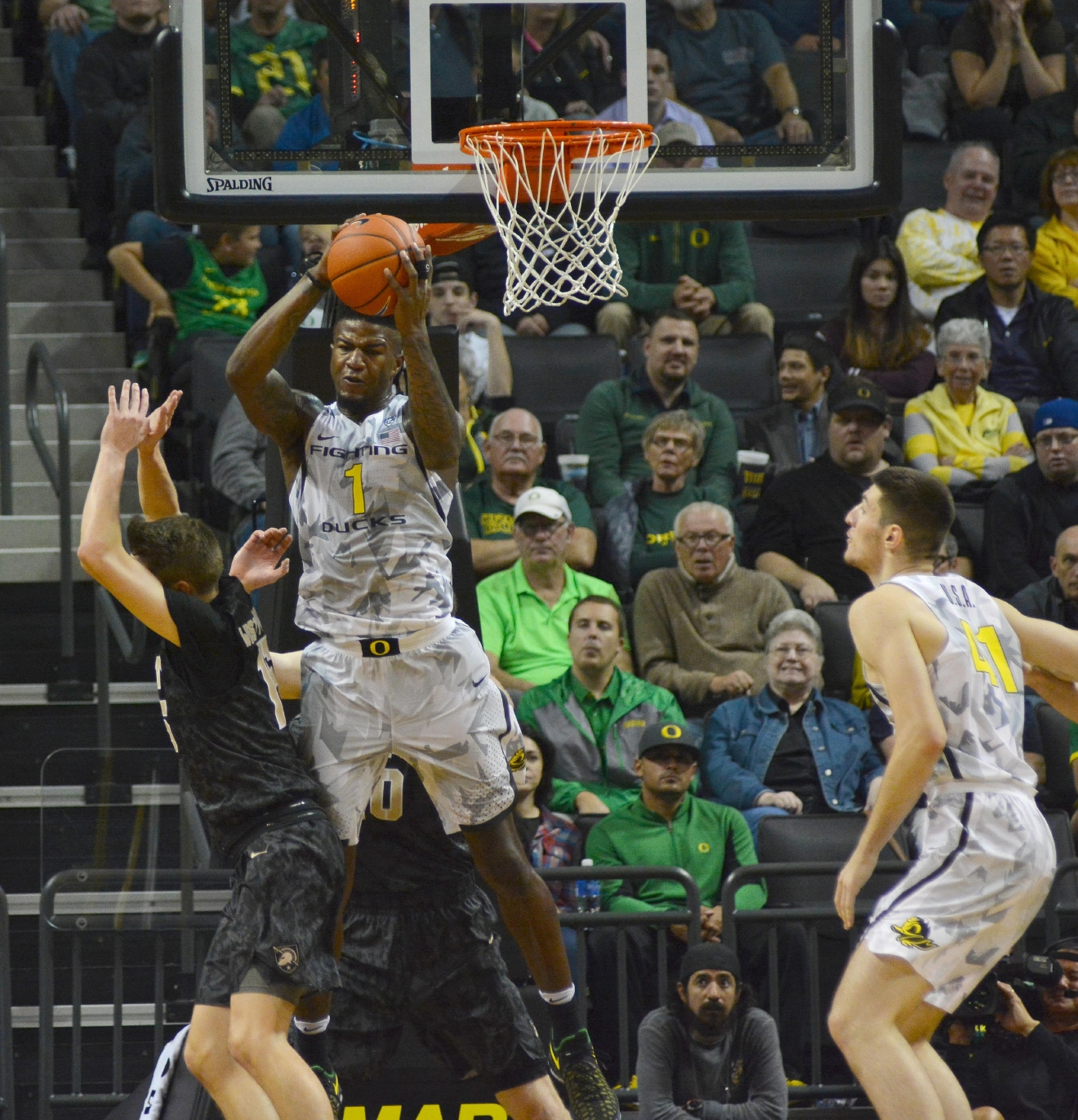 Ducks' Jordan Bell (#1) goes up big and comes down with a huge rebound. In front of a sold out crowd, Oregon defeated Army 91-77 on opening night. Photo by Jacob Smith, Oregon News Lab